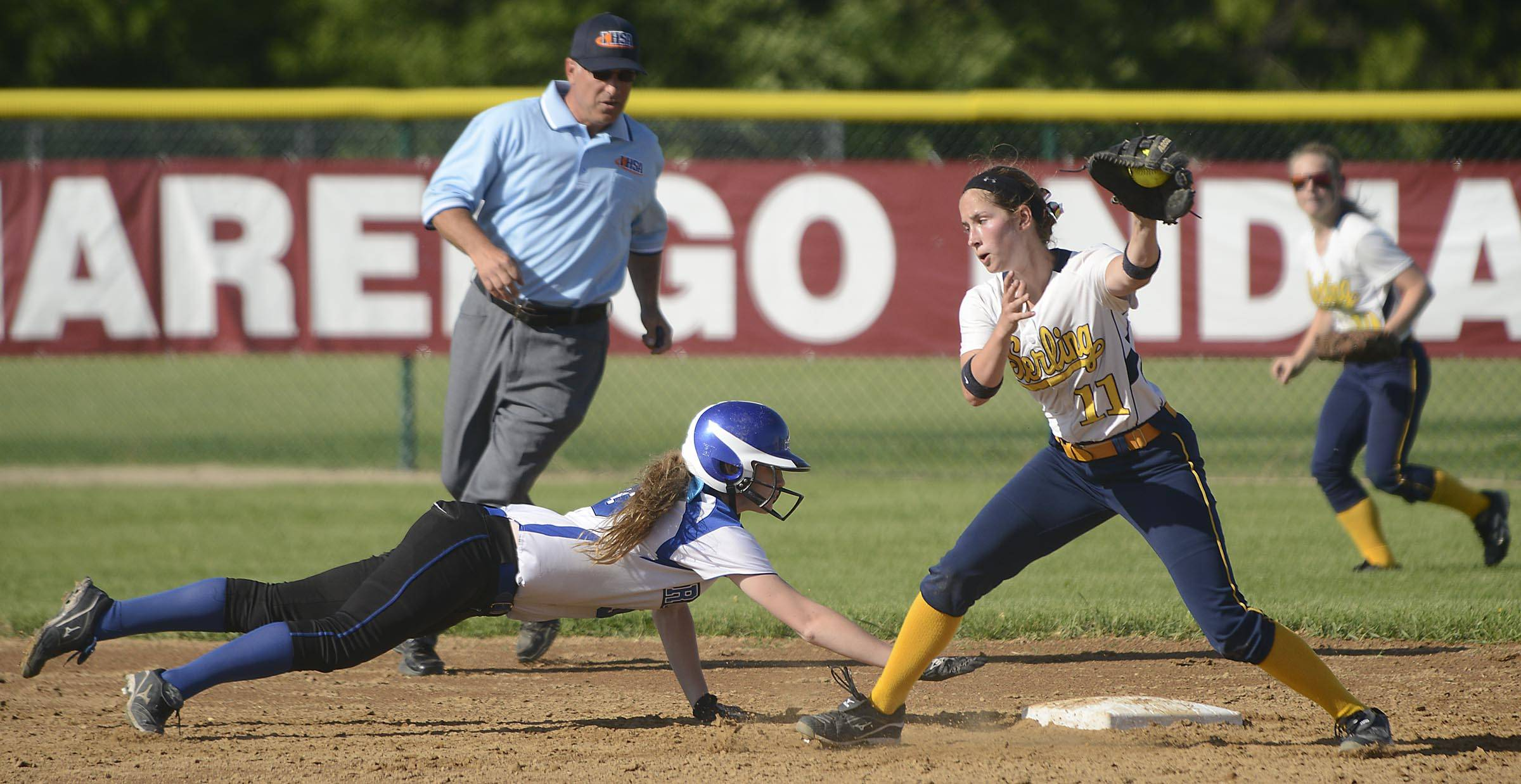Burlington Central's Rebecca Gerke dives safely back to second base as Sterling's Karlie Mellott grabs the throw Tuesday in the Class 3A Marengo sectional semifinal game.