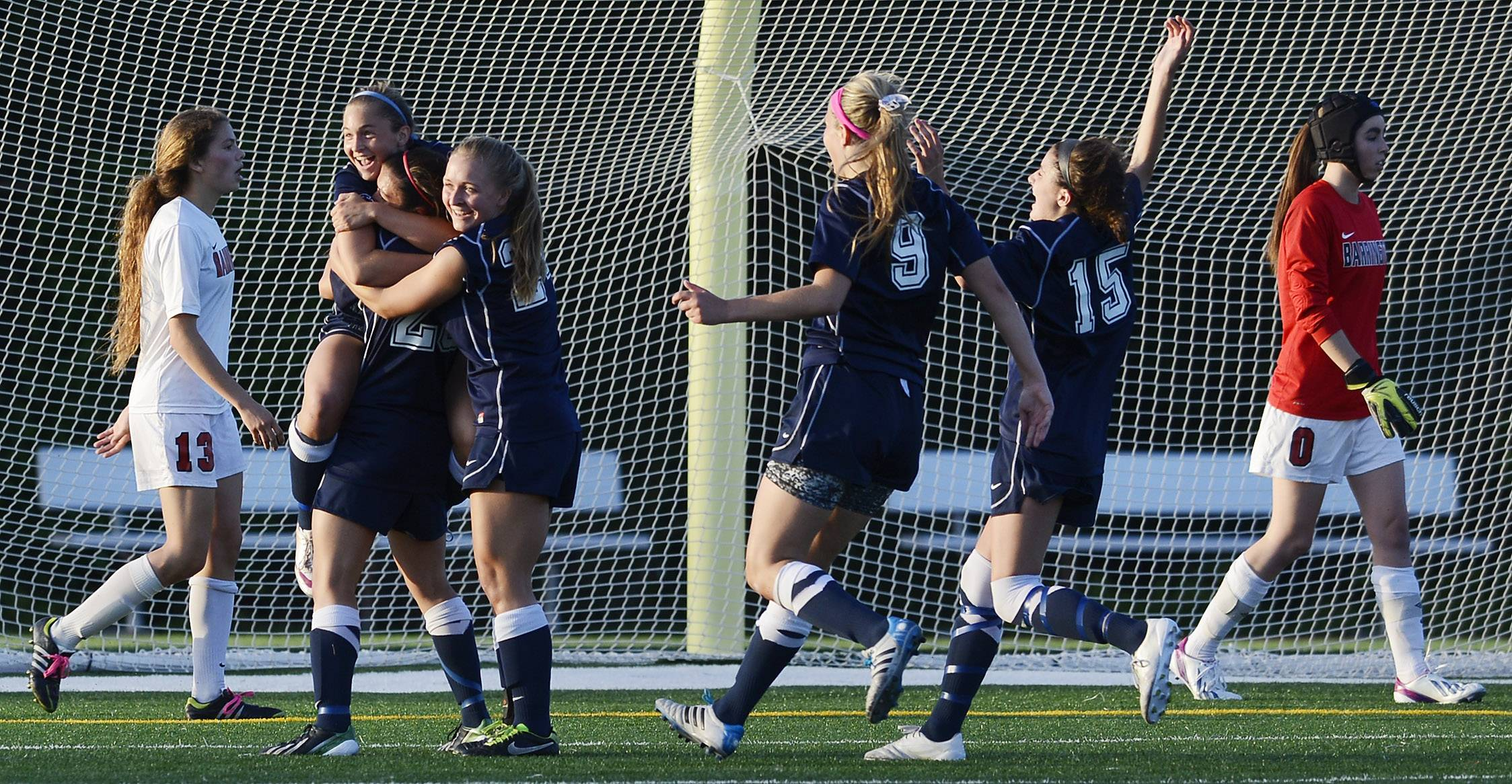 Barrington's Kelsey Muniz, left, and goalkeeper Hannah Luedtke, right, walk past New Trier players celebrating their team's goal during the Class 3A supersectional game at Hersey on Tuesday.