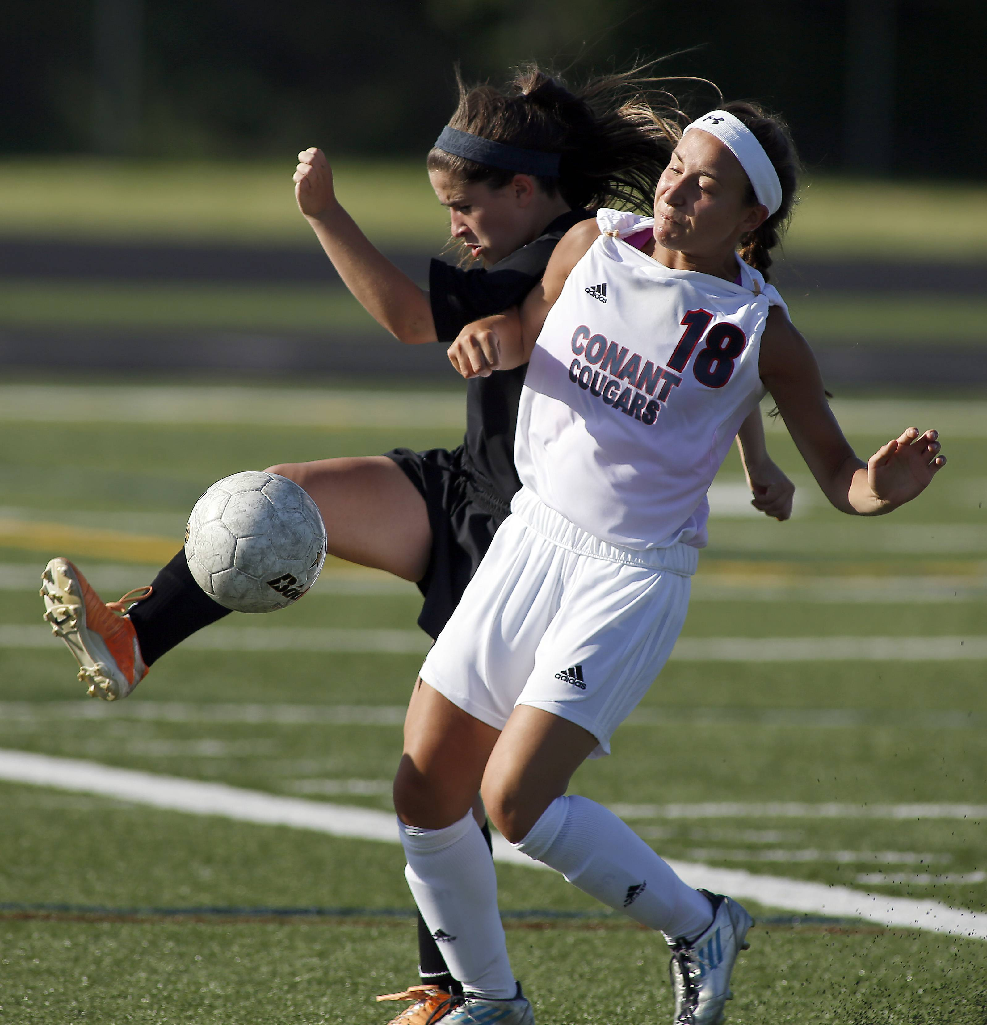 St. Charles East's Sara Buetow, 8, goes to battle against Conant's Emily Mazurek, 18, during St. Charles East vs. Conant girls soccer sectional title game Friday in Hoffman Estates.