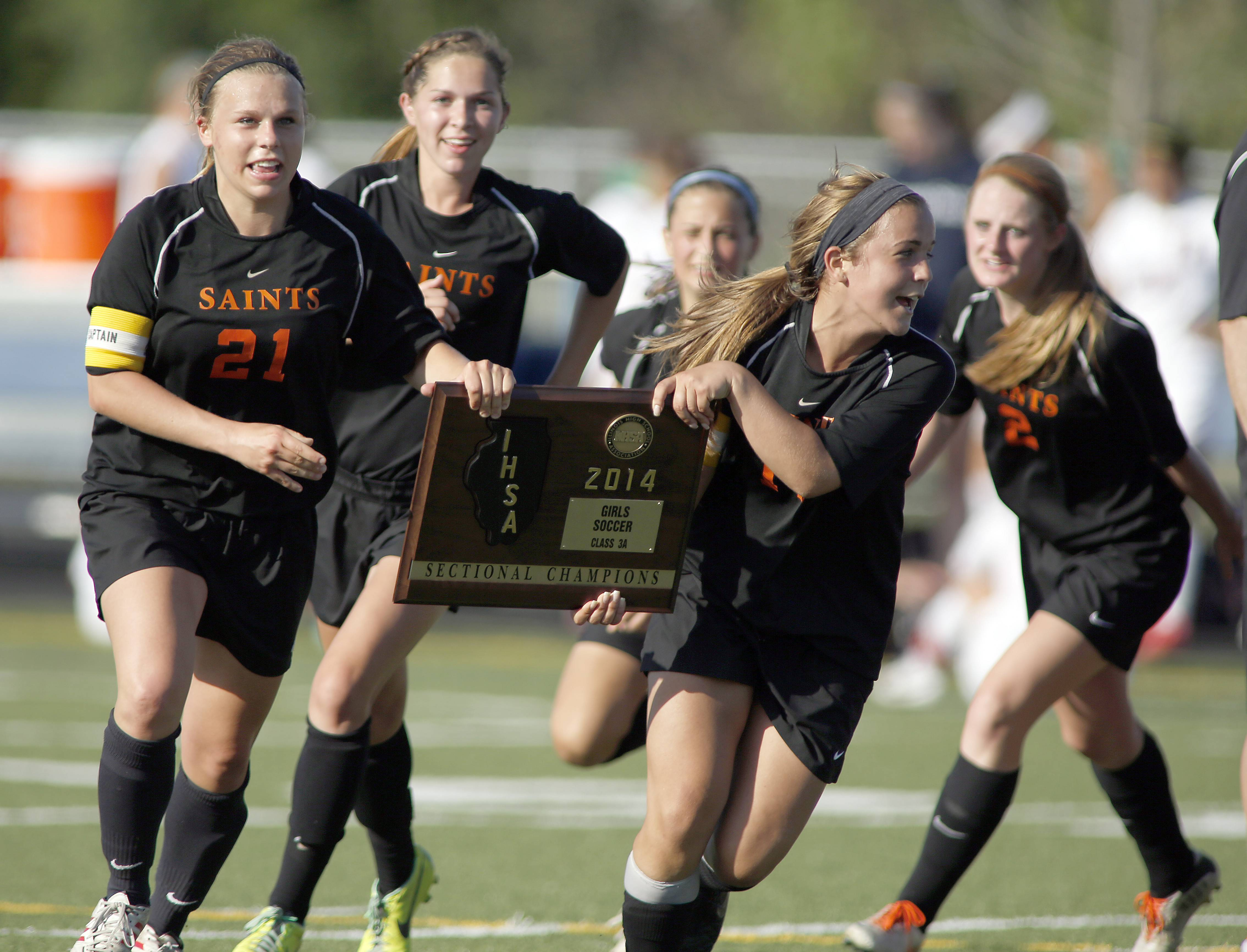 St. Charles East players rush to the sidelines with their plaque after beating Conant during girls soccer sectional championships Friday in Hoffman Estates.