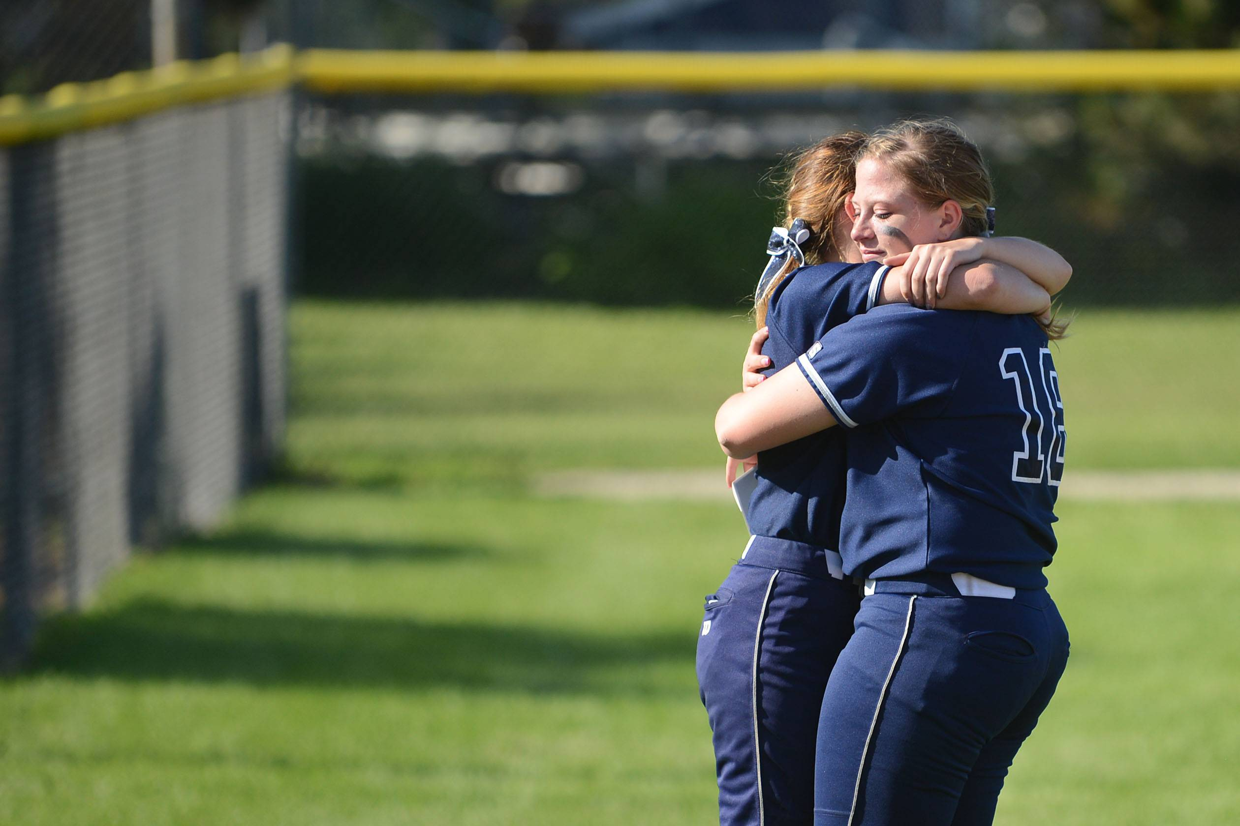 Cary-Grove's Colleen Kaveney, left, gives a comforting hug to a teary-eyed Caroline Zasadil after their 10-0 loss to Barrington in the Class 4A girls softball regional championship in Cary on Friday, May 30.