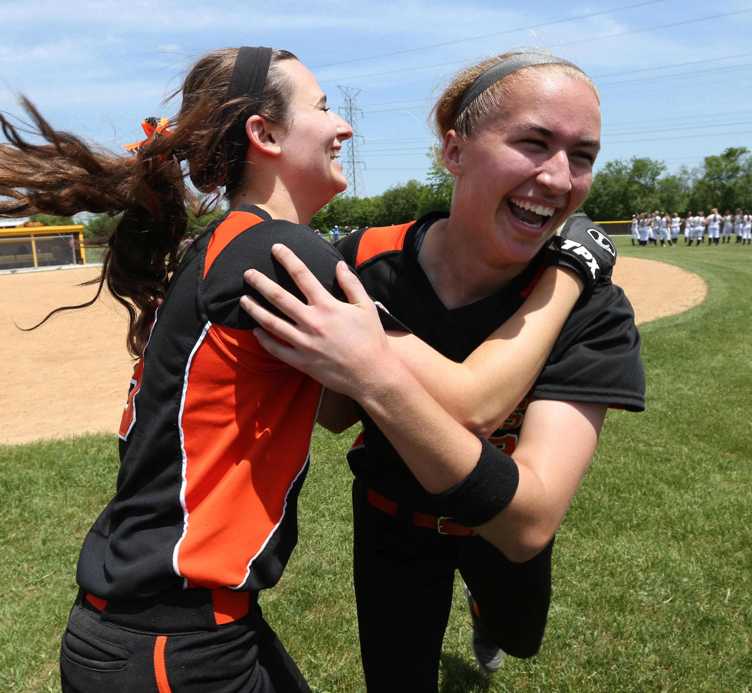 Libertyville's Tayler Oberman, right, gets a hug from teammate catcher Andi Katz after she hit a walk-off single to win the game against Carmel in a Class 4A Carmel softball regional final.