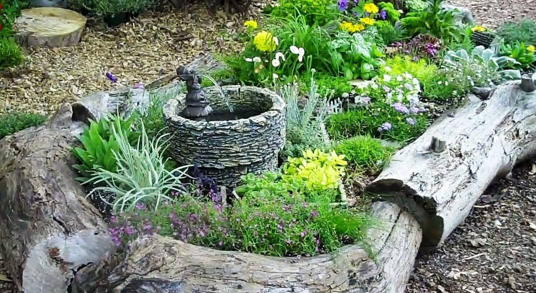 A small fountain is the focal point in this fairy garden.