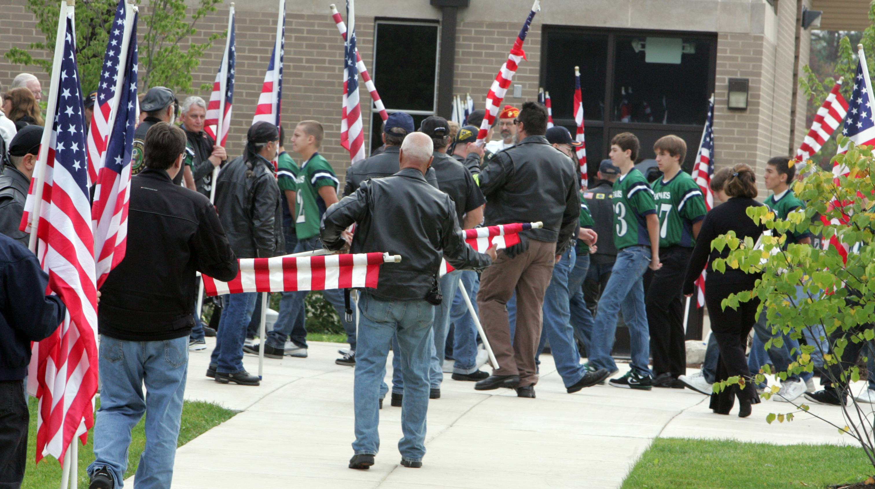 Bartlett High School football players enter St. Hubert Catholic Church as Patriot Guard Riders roll up their American flags after they were lined up at the entrance to the church for the mass of Matthew Martinek, a Bartlett High School graduate, on Saturday, Sept. 26. U.S. Army Pfc. Martinek died of injuries while serving in Afghanistan.