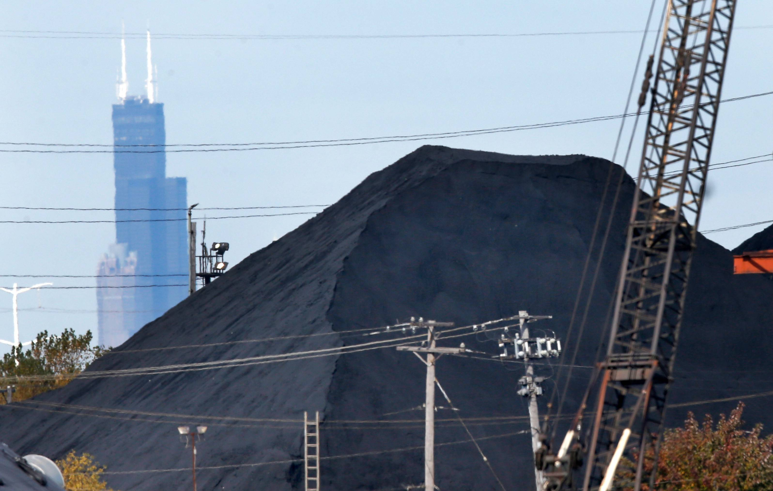 The Willis Tower in downtown Chicago provides a backdrop to a huge mound of petroleum coke in a residential area on the Southeast Side.
