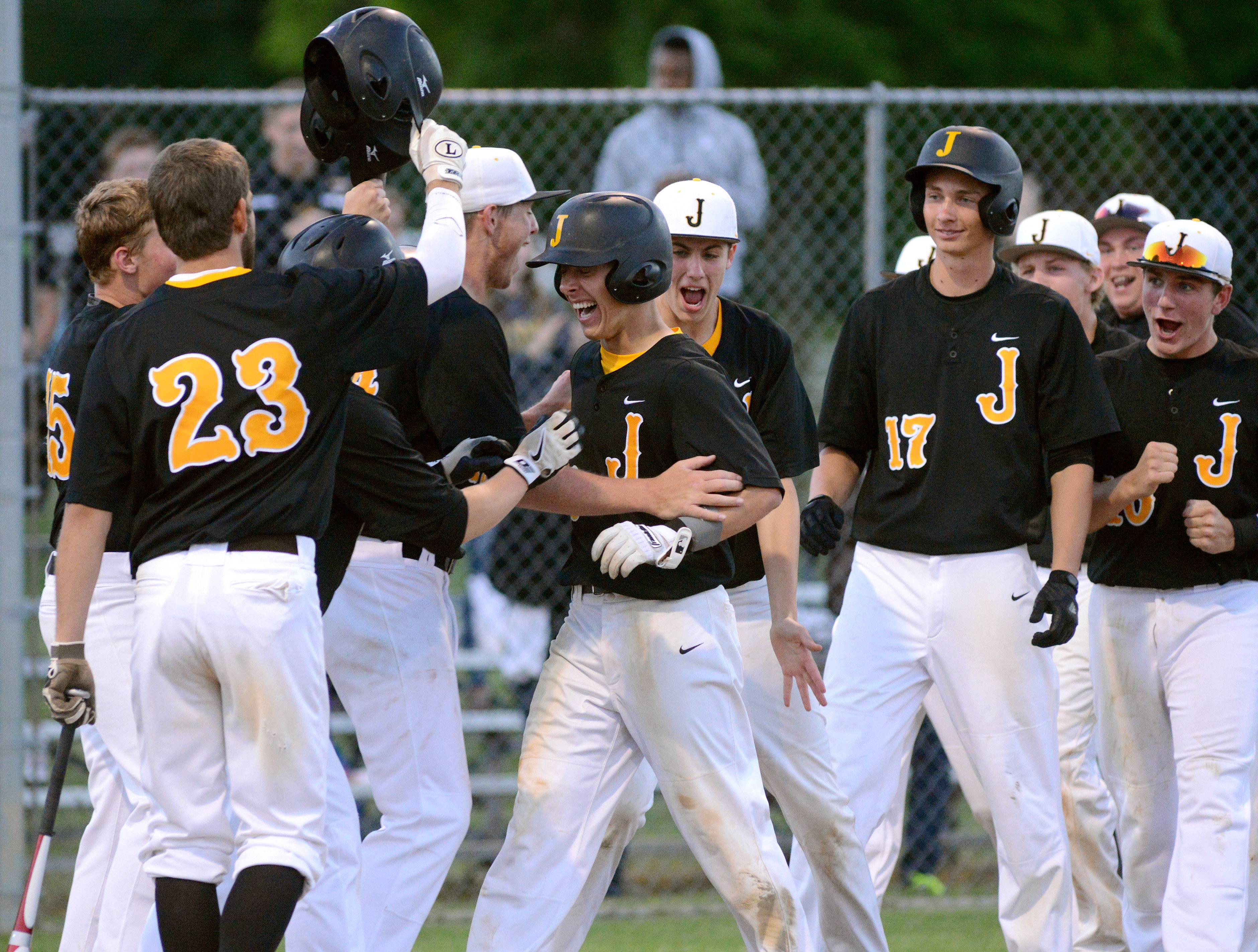 Jacobs' Matt Kozlak, center, is greeted by teammates at home plate after hitting a home run in the fifth inning vs. Hononegah in the Class 4A McHenry sectional semifinal on Wednesday.
