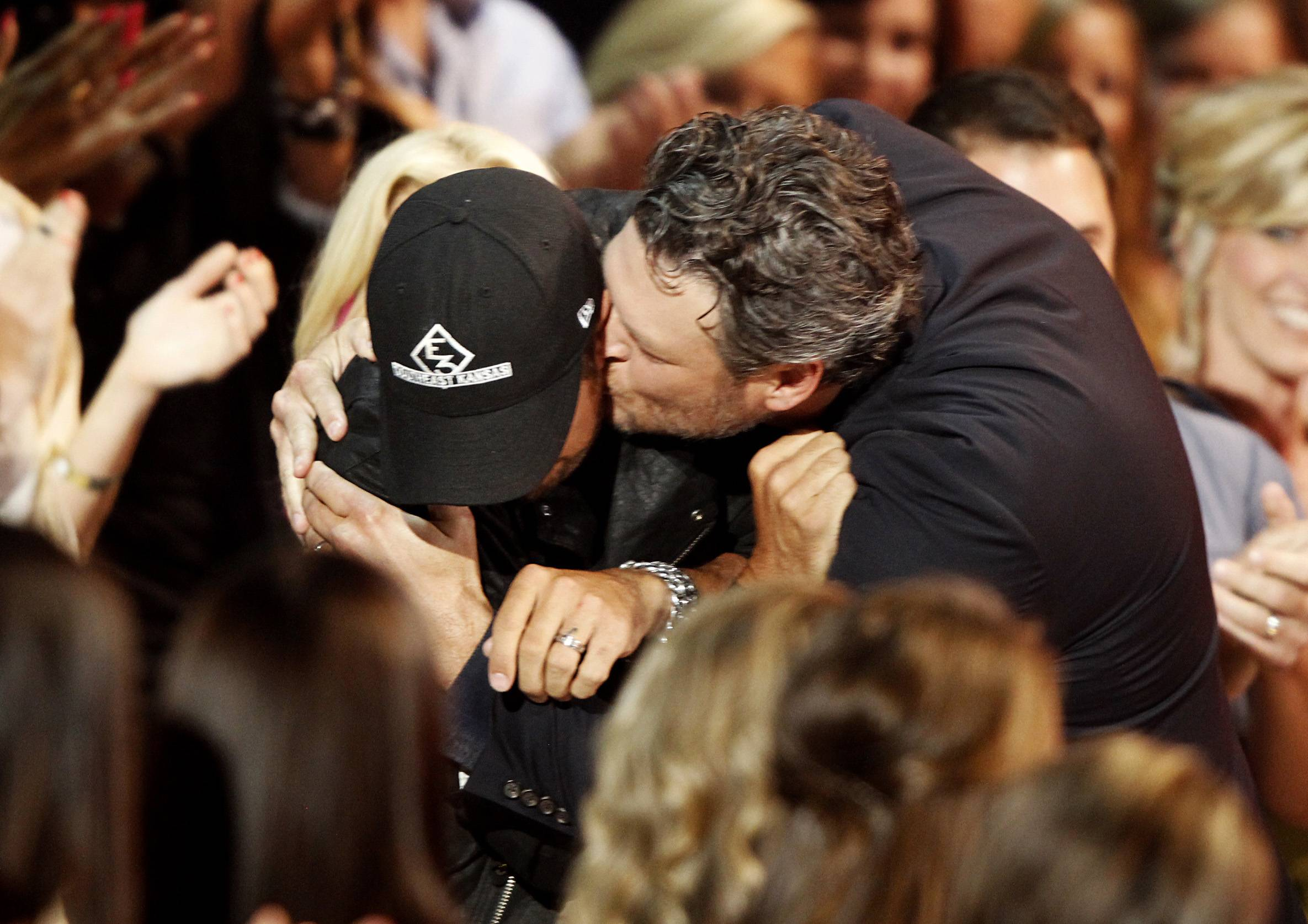 "Blake Shelton, right, kisses Luke Bryan in the audience as he walks to the stage to accept his award for male video of the year for ""Doin' What She Likes."""