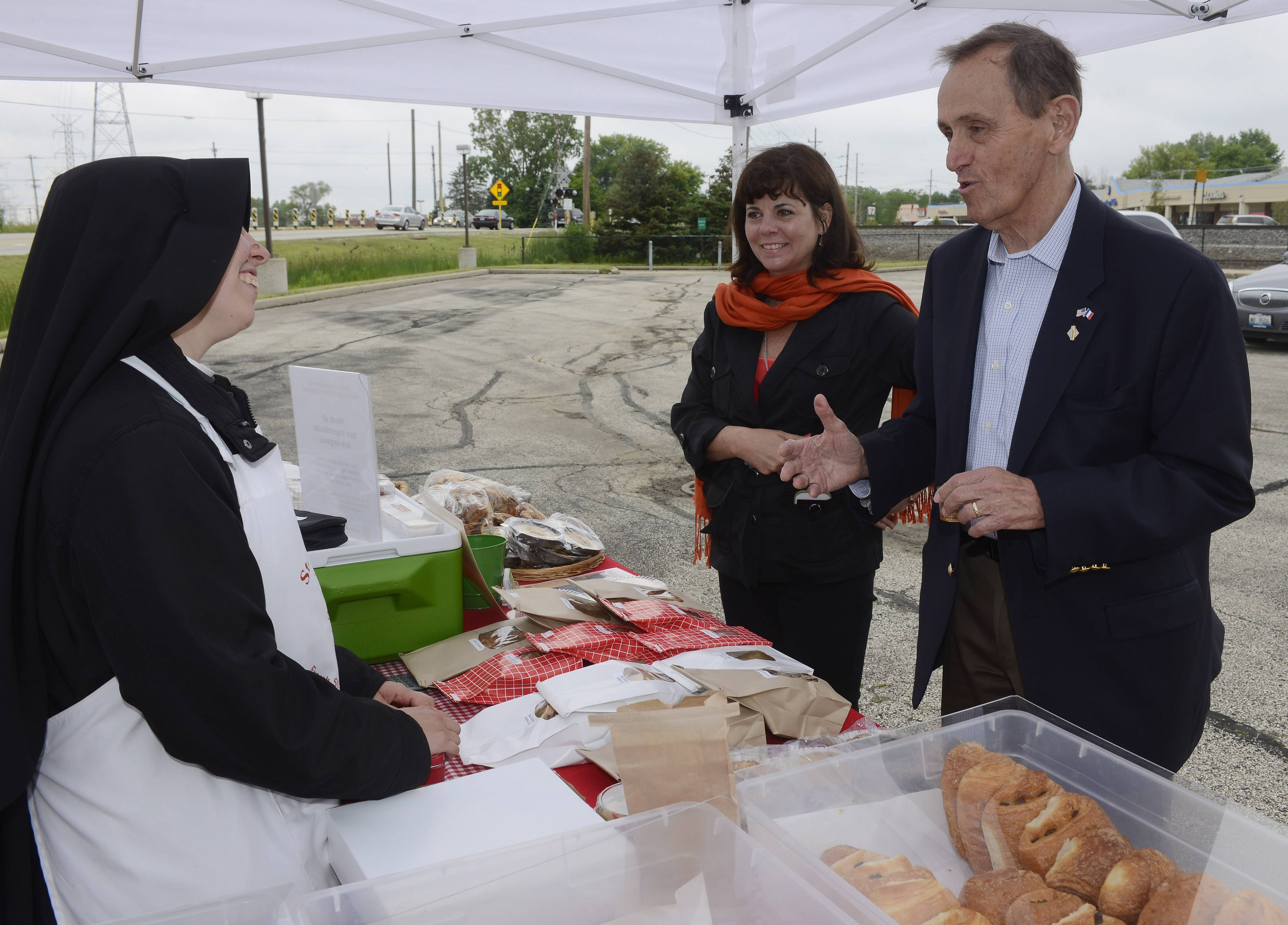 Prospect Heights Mayor Nick Helmer and Leslie Cahill, middle, of French Market of Chicago LLC visit with Sister Marie of St. Rogers Abbey as she sells baked goods Wednesday during the French Market at the Prospect Heights Metra station parking lot.