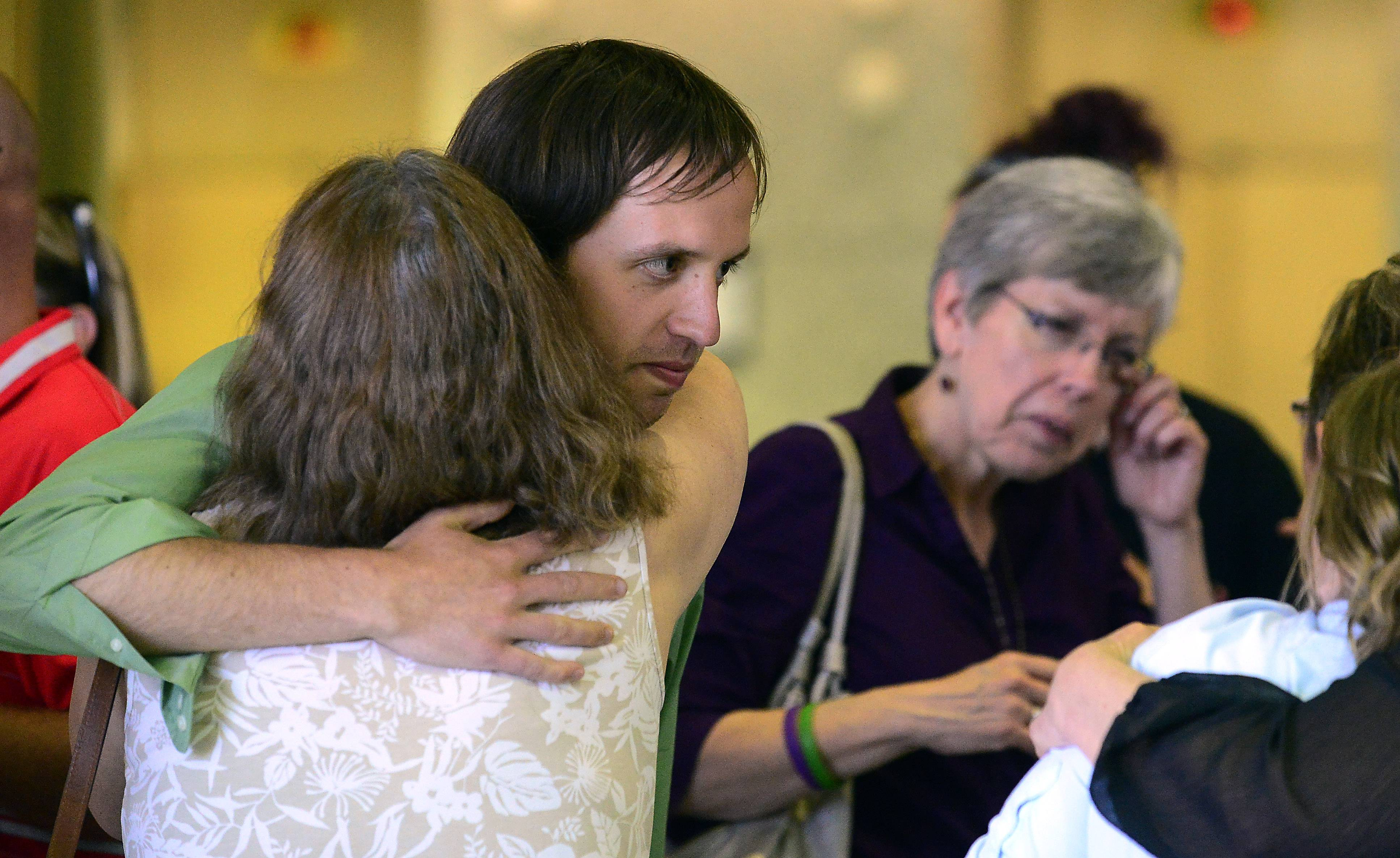 An emotional Jeff Engelhardt gets hugs from supporters as his mother Shelly wipes away tears after D'Andre Howard's conviction Tuesday. Howard was found guilty on all counts in the 2009 stabbing deaths of three members of the Engelhardt family in their Hoffman Estates home.