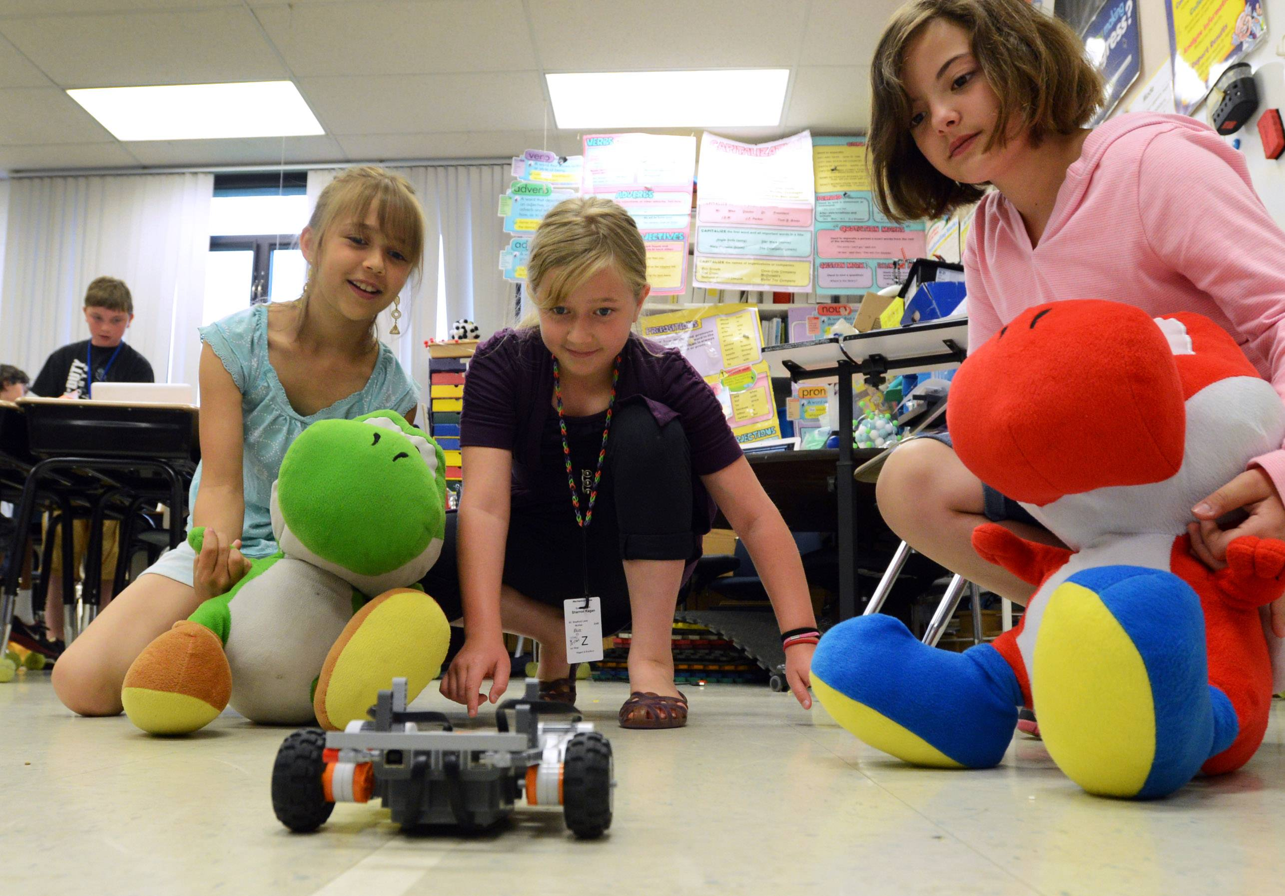 Isabella Hagglund, left, Sharron Kagan and Gina Cosentino, all incoming fourth grade students, try out their Lego robot Wednesday during the Summer Enrichment Program at Mechanics Grove School.