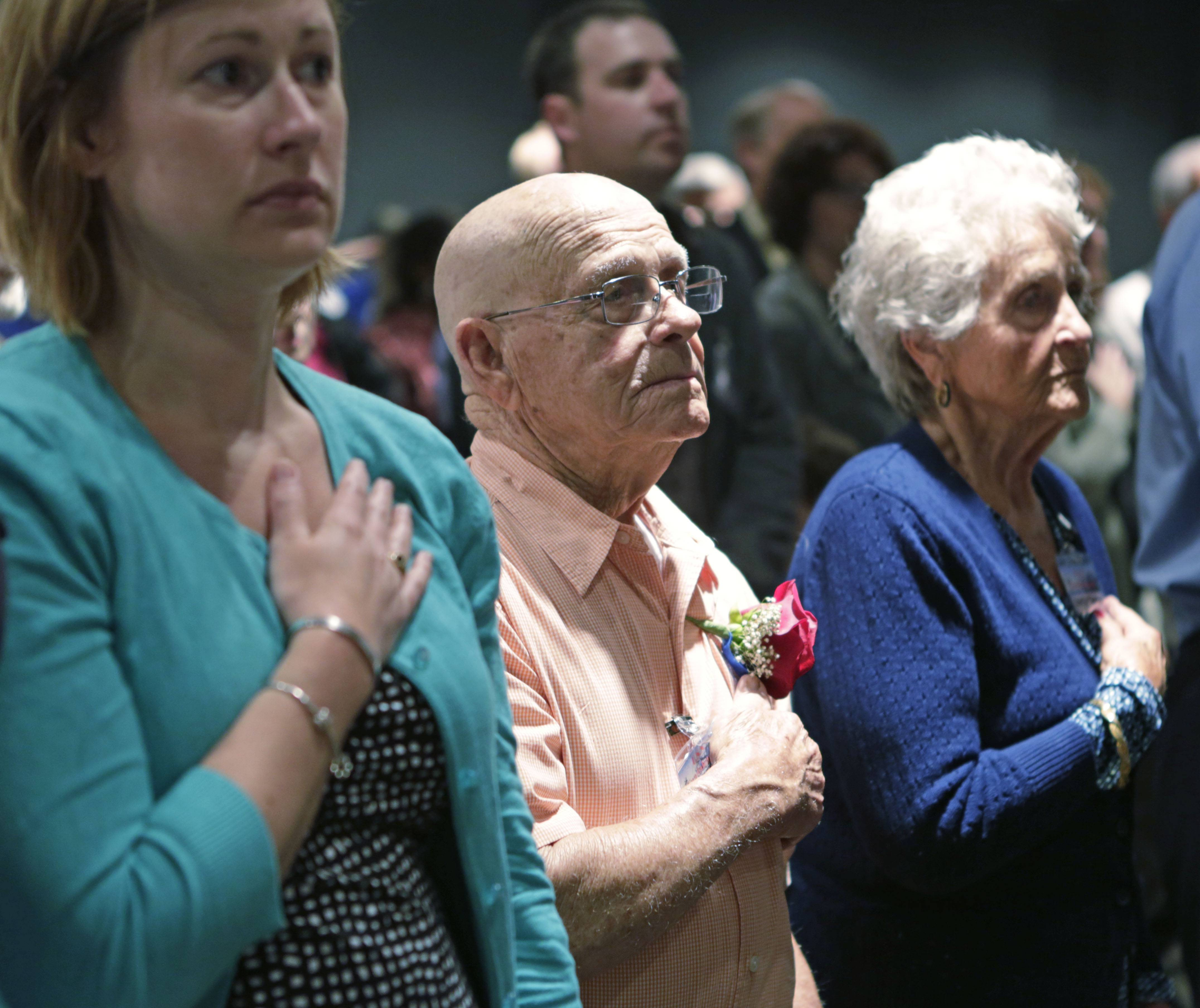 World War II veteran Doug Thrutchley, center, stands for the national anthem during a ceremony Wednesday to mark the 70th anniversary of the capture of the U-505 German submarine on display at Chicago's Museum of Science and Industry.