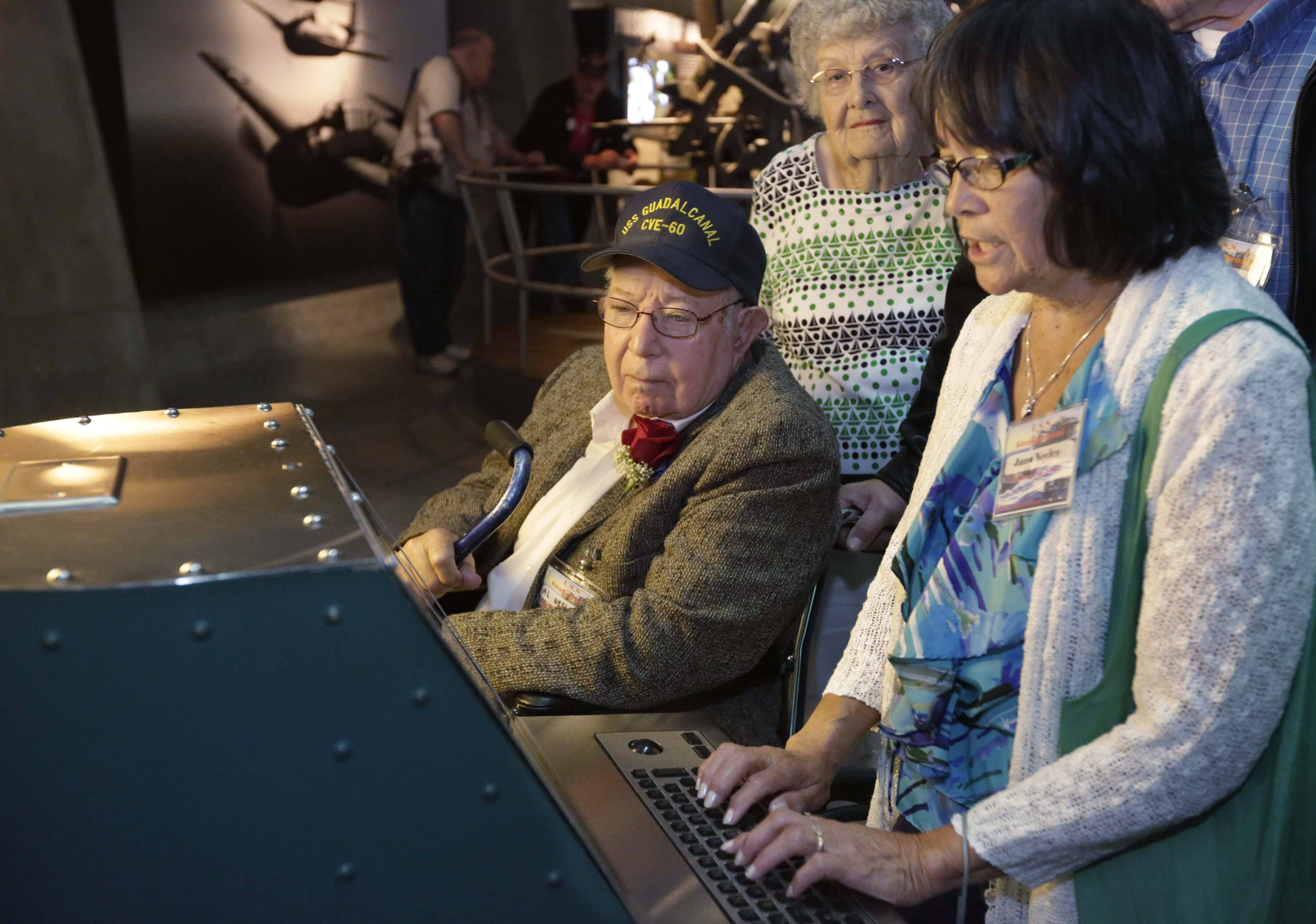 World War II veteran Al Neeley of Puyallup, Wash., watches as his daughter-in-law, Jan Neeley, types on an Enigma code machine Wednesday at the interactive exhibits by the captured U-505 German submarine on display at Chicago's Museum of Science and Industry.