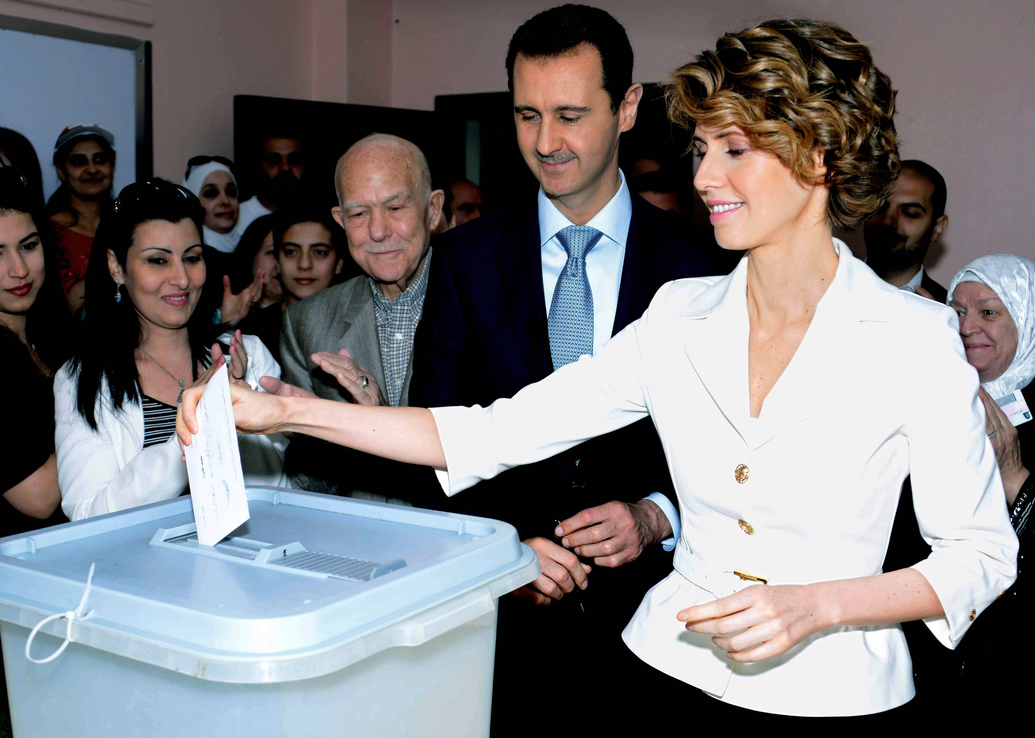 In this photo released by the Syrian official news agency SANA, Syrian first lady Asma Assad, right, casts her vote as  Syrian President Bashar Assad, stands next to her at a polling station in Damascus, Syria, Tuesday. Assad was re-elected in a landslide, officials said Wednesday.