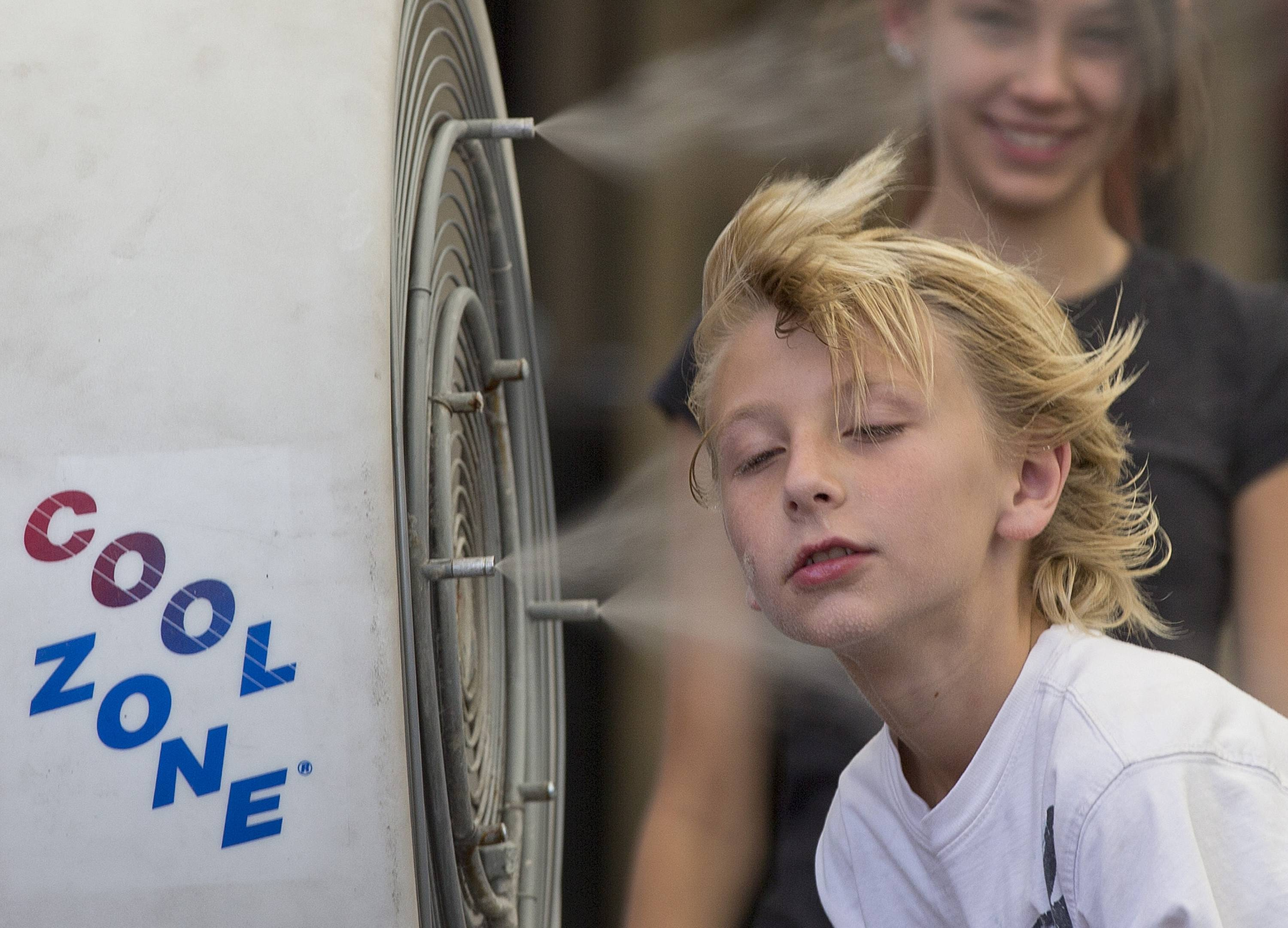 Easton Martin, 10, of Mesa, Ariz., stops to cool off in a misting fan while walking along The Strip with his family in Las Vegas in June 2013. An Associated Press analysis of federal temperature records shows Nevada's capital city, Carson City has warmed the most in the last 30 years than any other city in the nation.