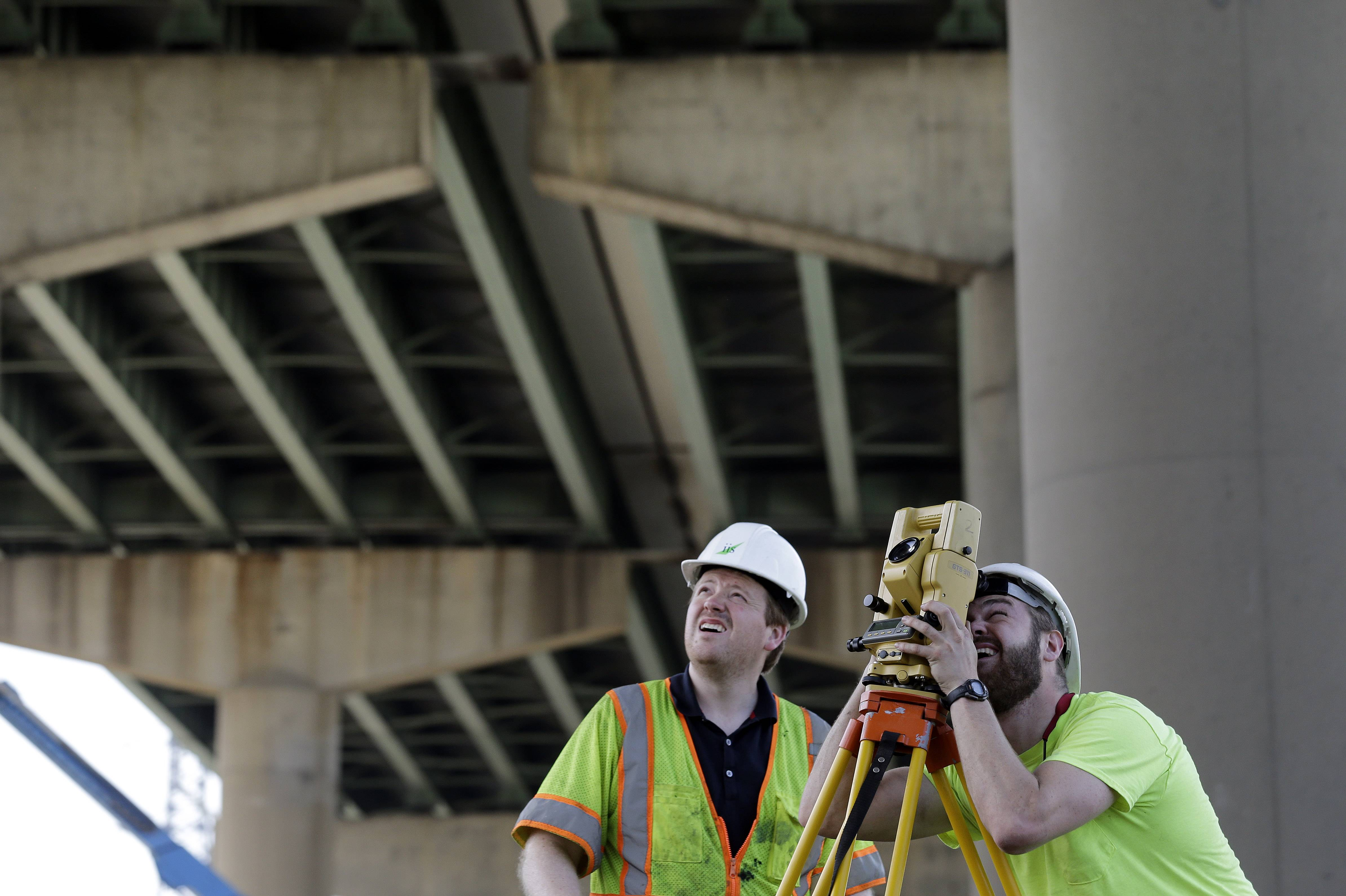 Surveyors work below the Interstate 495 bridge over the Christina River near Wilmington, Del., Tuesday, June 3, 2014, after it was closed due to the discovery of four tilting support columns.