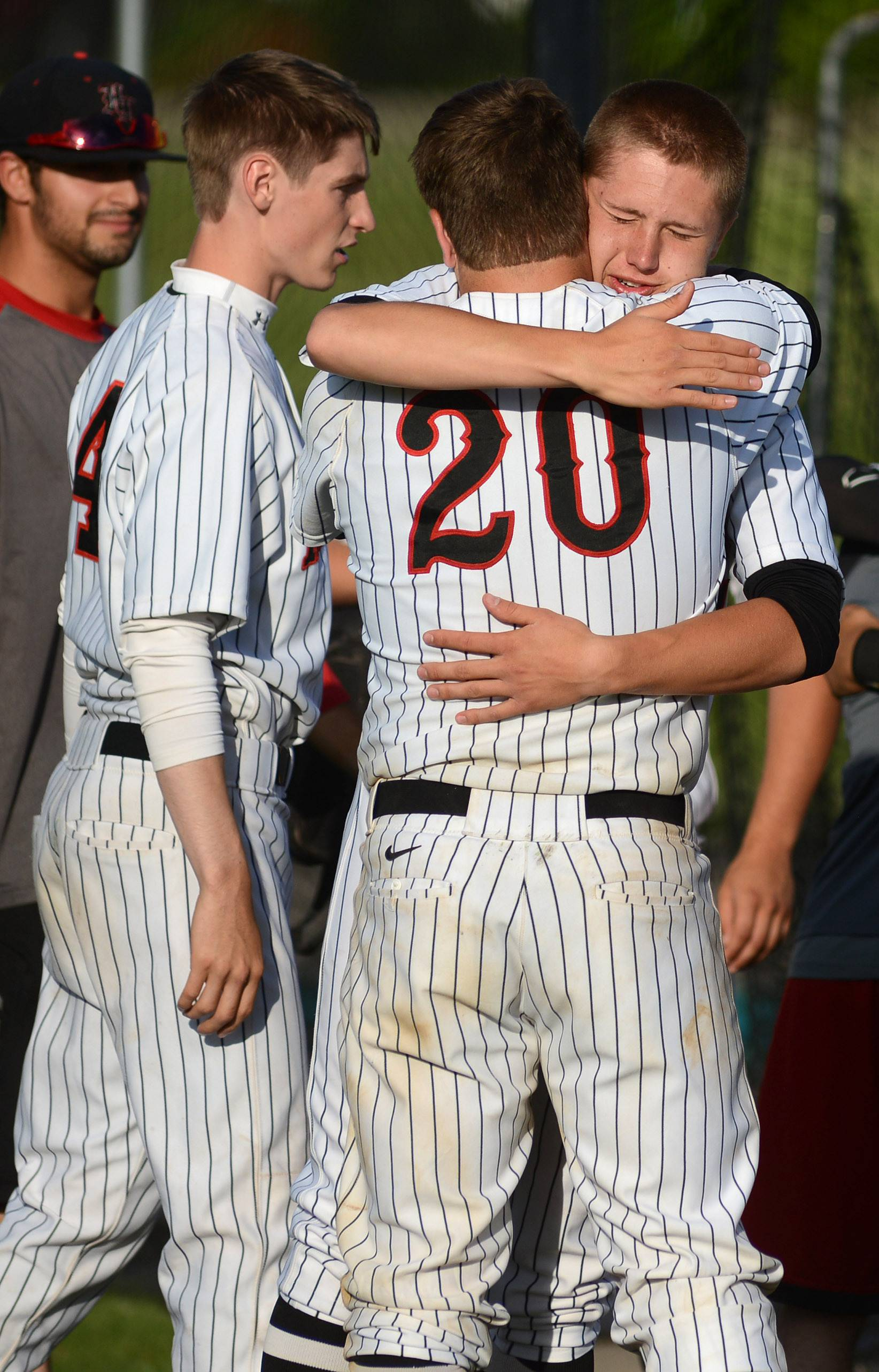 Huntley's Mark Skonieczny (20) gets a hug from teammate Mason Martin (facing) after their loss to Prairie Ridge in the Class 4A McHenry sectional semifinal on Wednesday, June 4. Both are seniors.