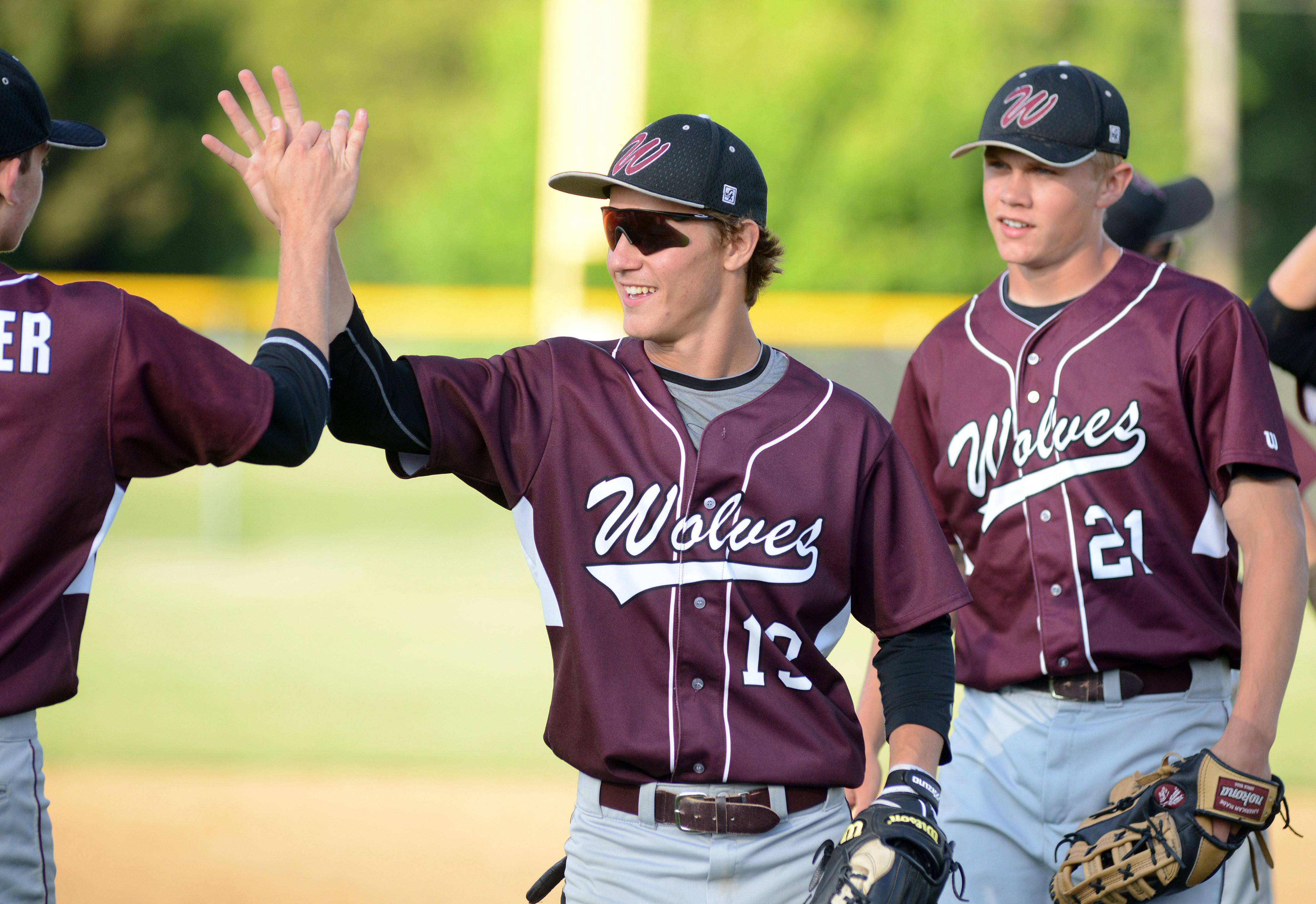 Prairie Ridge's Connor Schneider, left, high fives Kyle Buresch (facing) as they come off the field winning the game vs. Huntley in the Class 4A McHenry sectional semifinal on Wednesday, June 4.