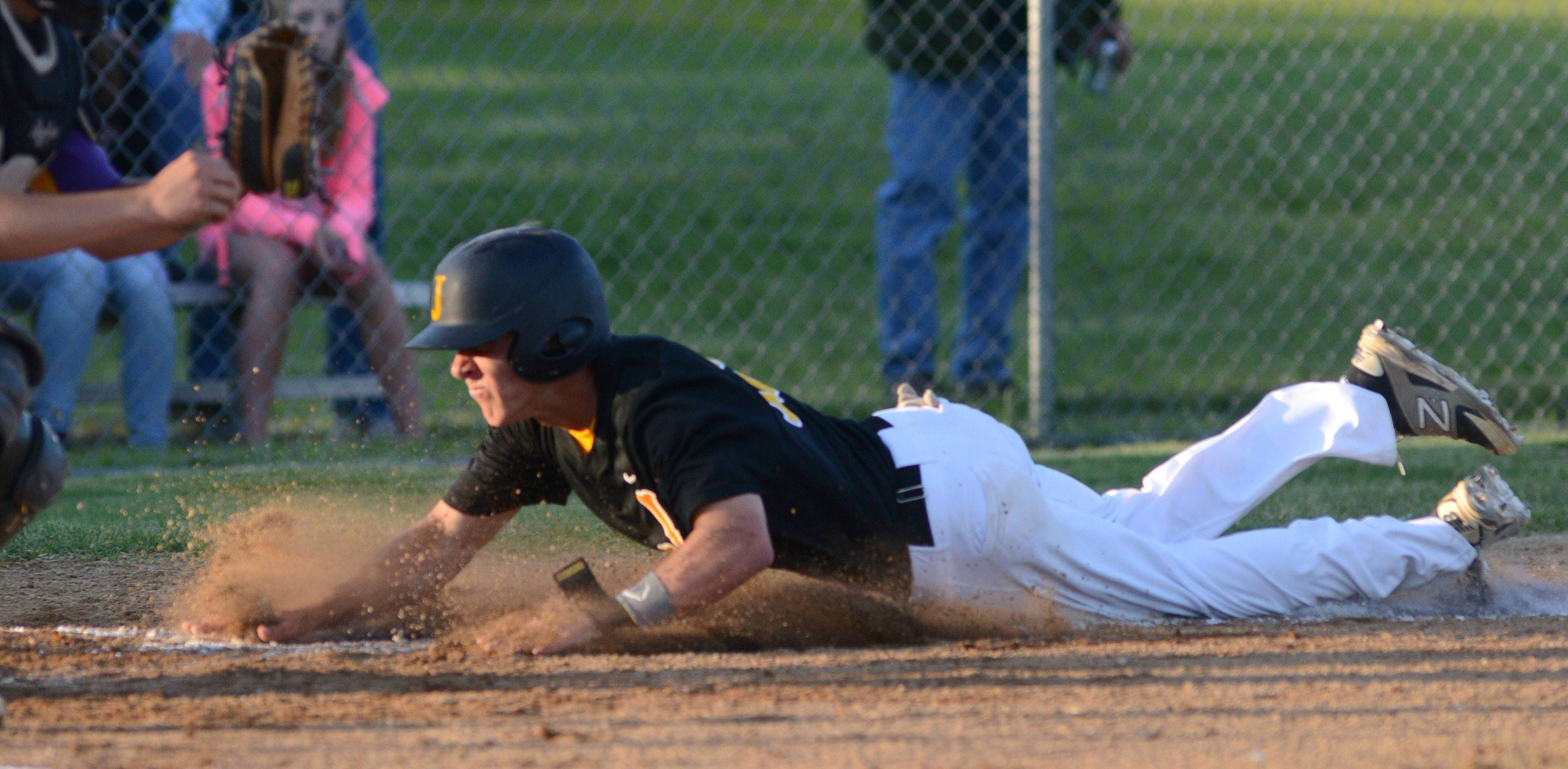 Jacobs' Matt Kozlak slides into home plate in the first inning, scoring the first run for the team vs. Hononegah in the Class 4A McHenry sectional semifinal on Wednesday, June 4.
