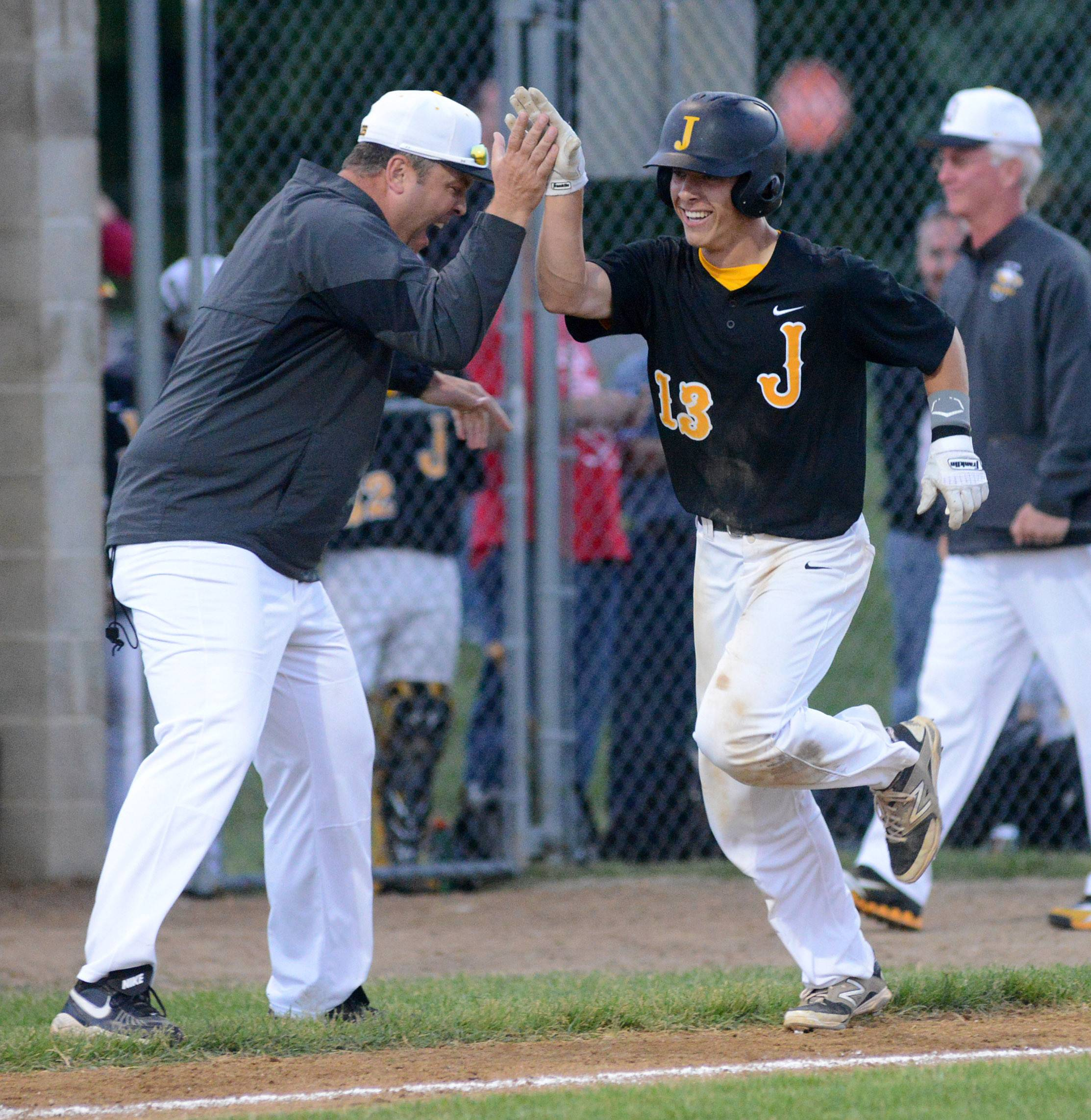 Jacobs' Matt Kozlak gets a high five from one of his coaches as he heads for home plate after hitting a home run in the fifth inning vs. Hononegah in the Class 4A McHenry sectional semifinal on Wednesday, June 4.