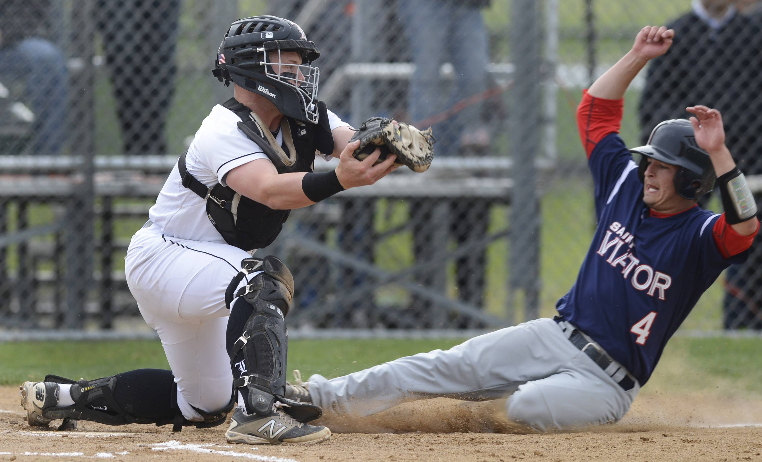 St. Viator's Matt Prazuch slides in safely with the game's first run as Libertyville catcher Evan Skoug takes the throw during Class 4A baseball sectional semifinal play at Glenbrook South on Wednesday.
