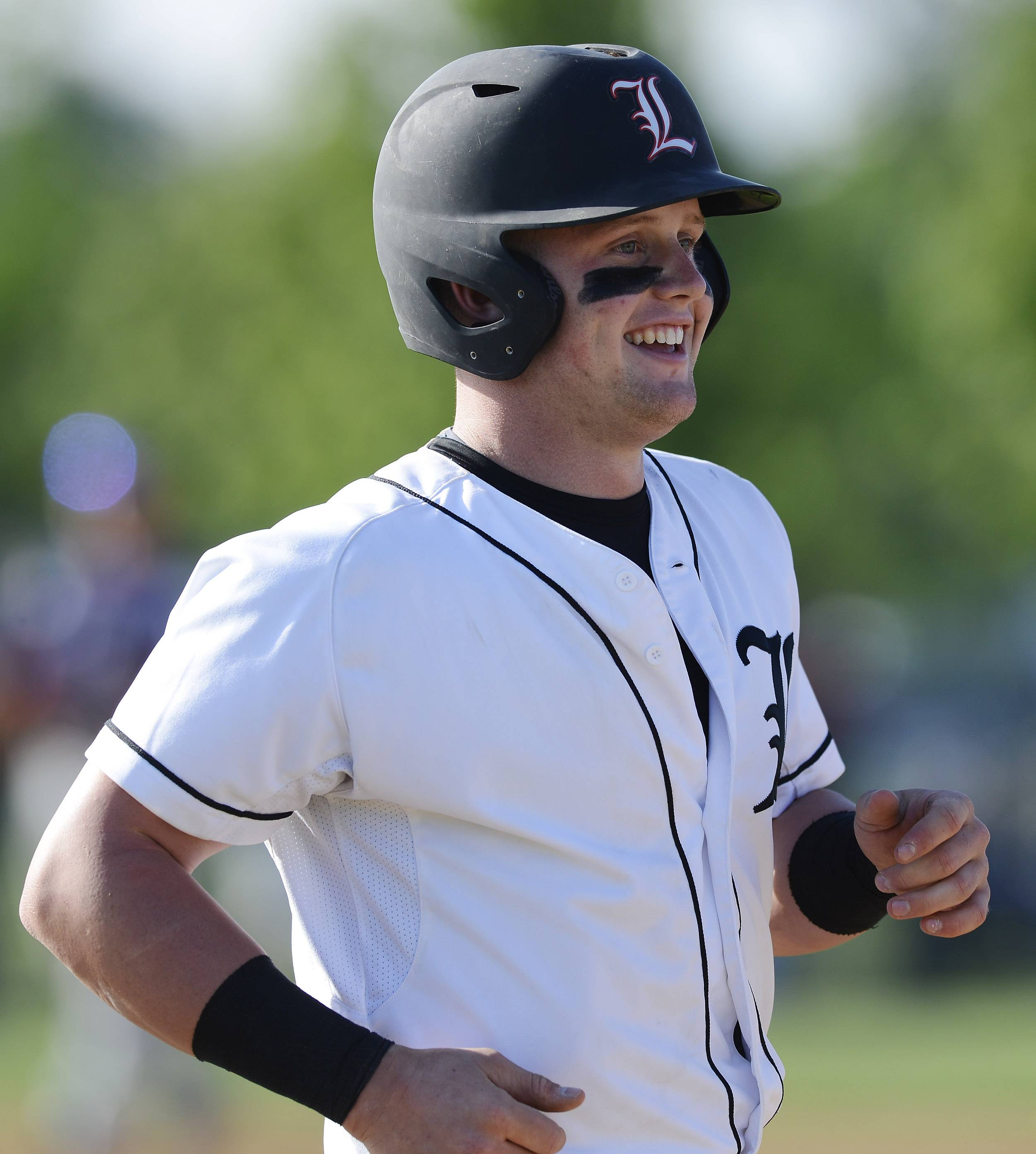 Libertyville's Evan Skoug smiles after drawing an intentional walk with runners on first and third during Class 4A baseball sectional semifinal play at Glenbrook South on Wednesday.