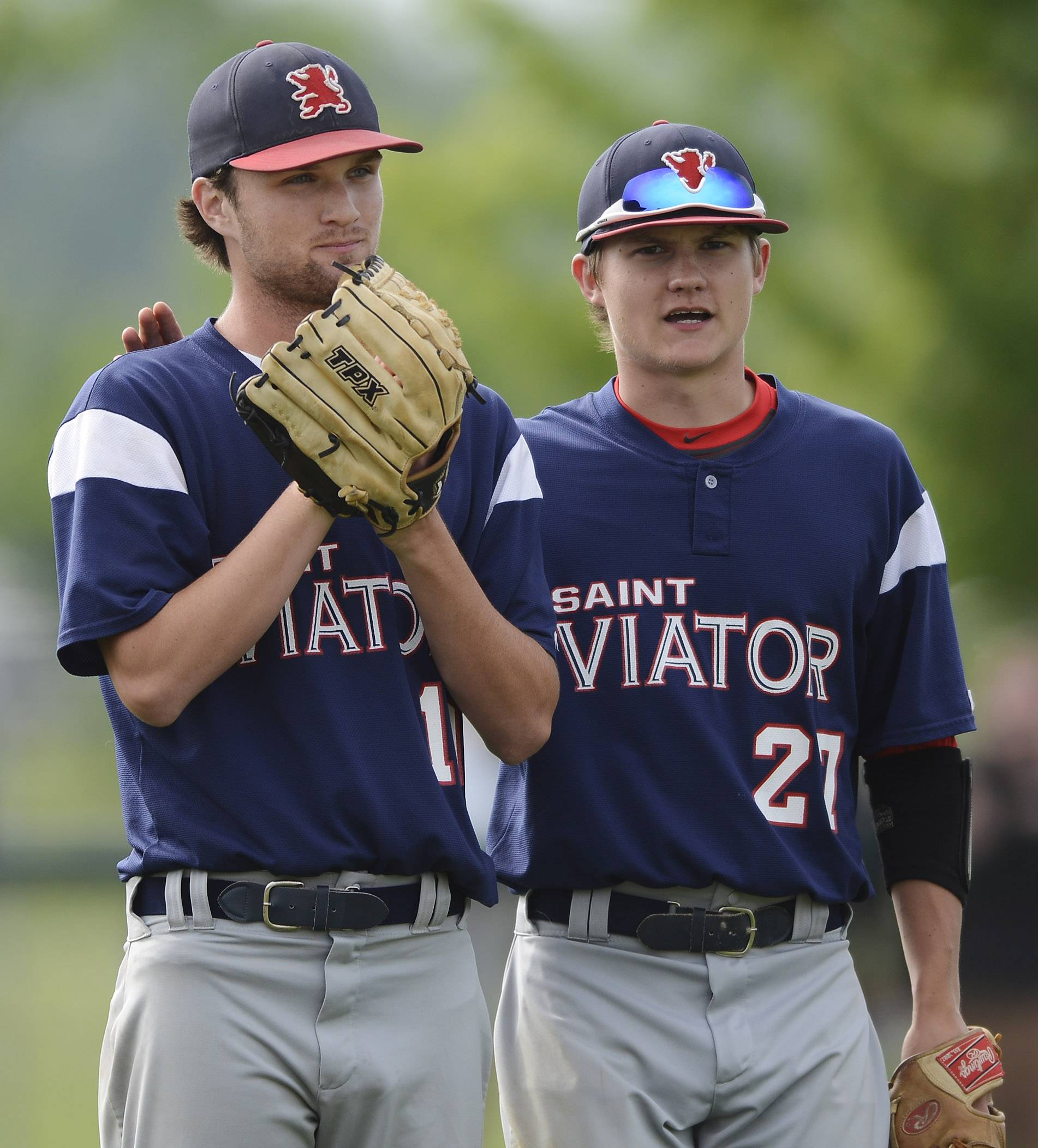 St. Viator pitcher Jack McElroy gets a pat on the back from third baseman Bobby Calmeyn after making an errant throw to first on a Libertyville bunt during Class 4A baseball sectional semifinal play at Glenbrook South on Wednesday.