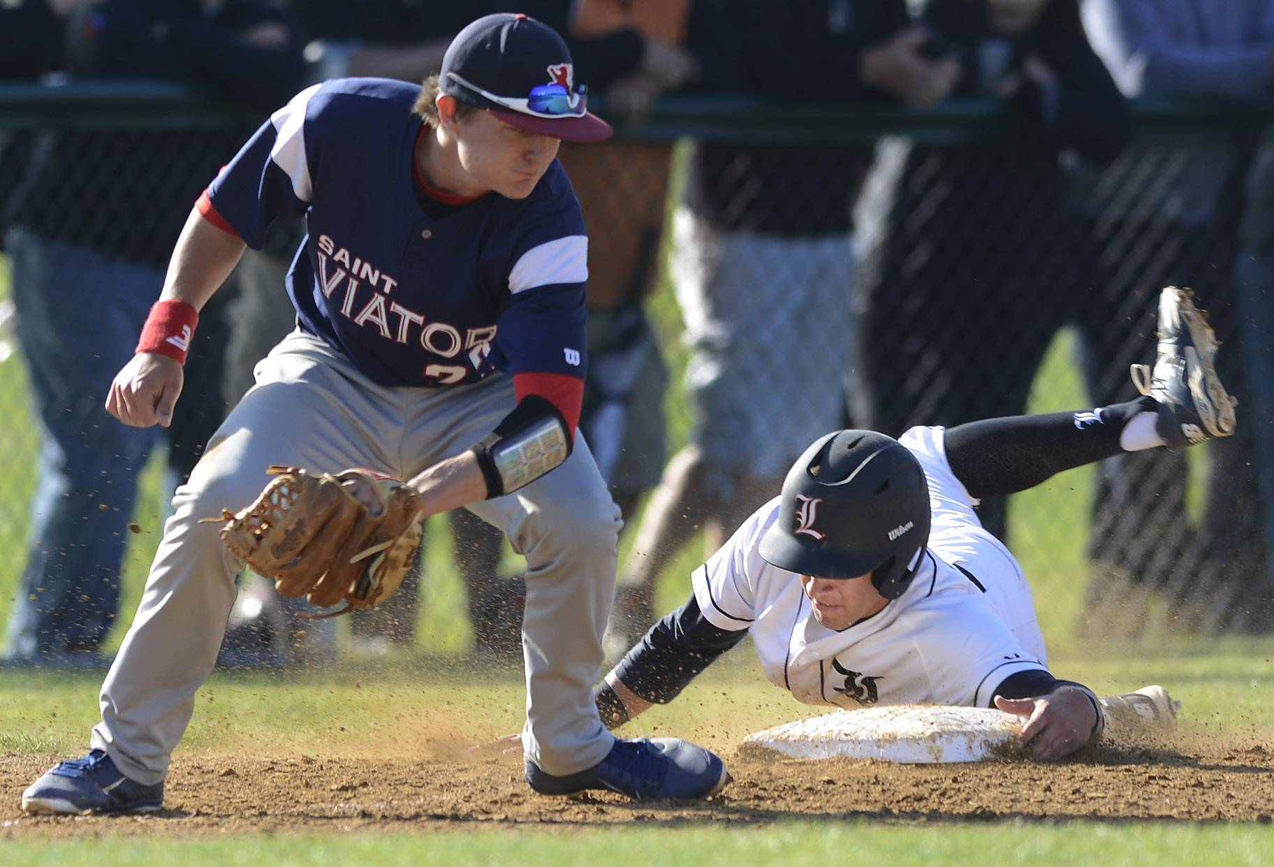 Libertyville's Jimmy Govern grabs the base on a steal of third as St. Viator third baseman Bobby Calmeyn takes the throw during Class 4A sectional semifinal play Wednesday at Glenbrook South.