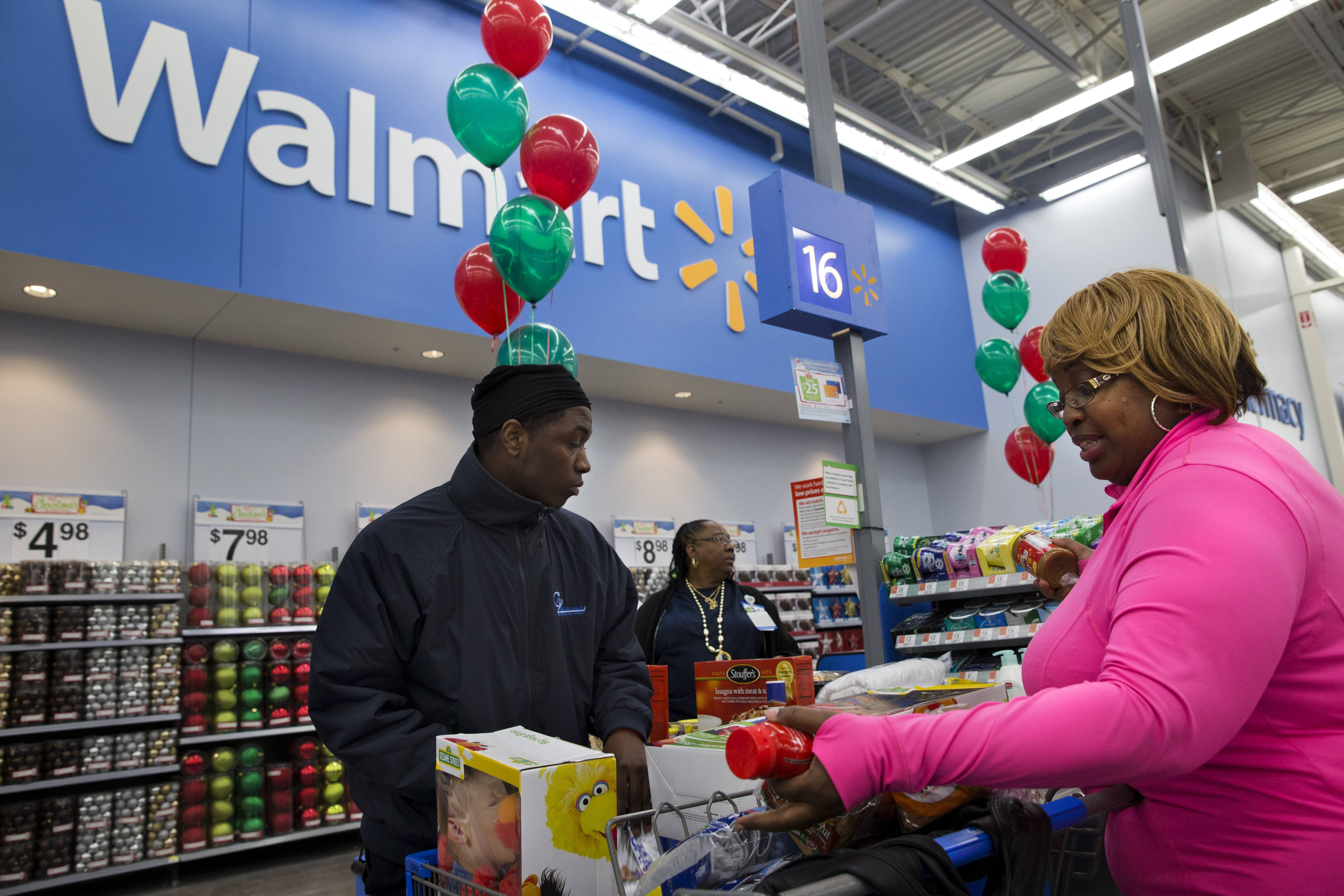 April Taylor, of Upper Marlboro, Md., right, buys items with her son Jarhon Taylor, left, on the opening day of a new Wal-Mart store in Washington. The world's largest retailer Wednesday said that it's expanding Savings Catcher, its online tool that compares prices on thousands of products with those of some of its competitors to cities nationwide in the next few months.