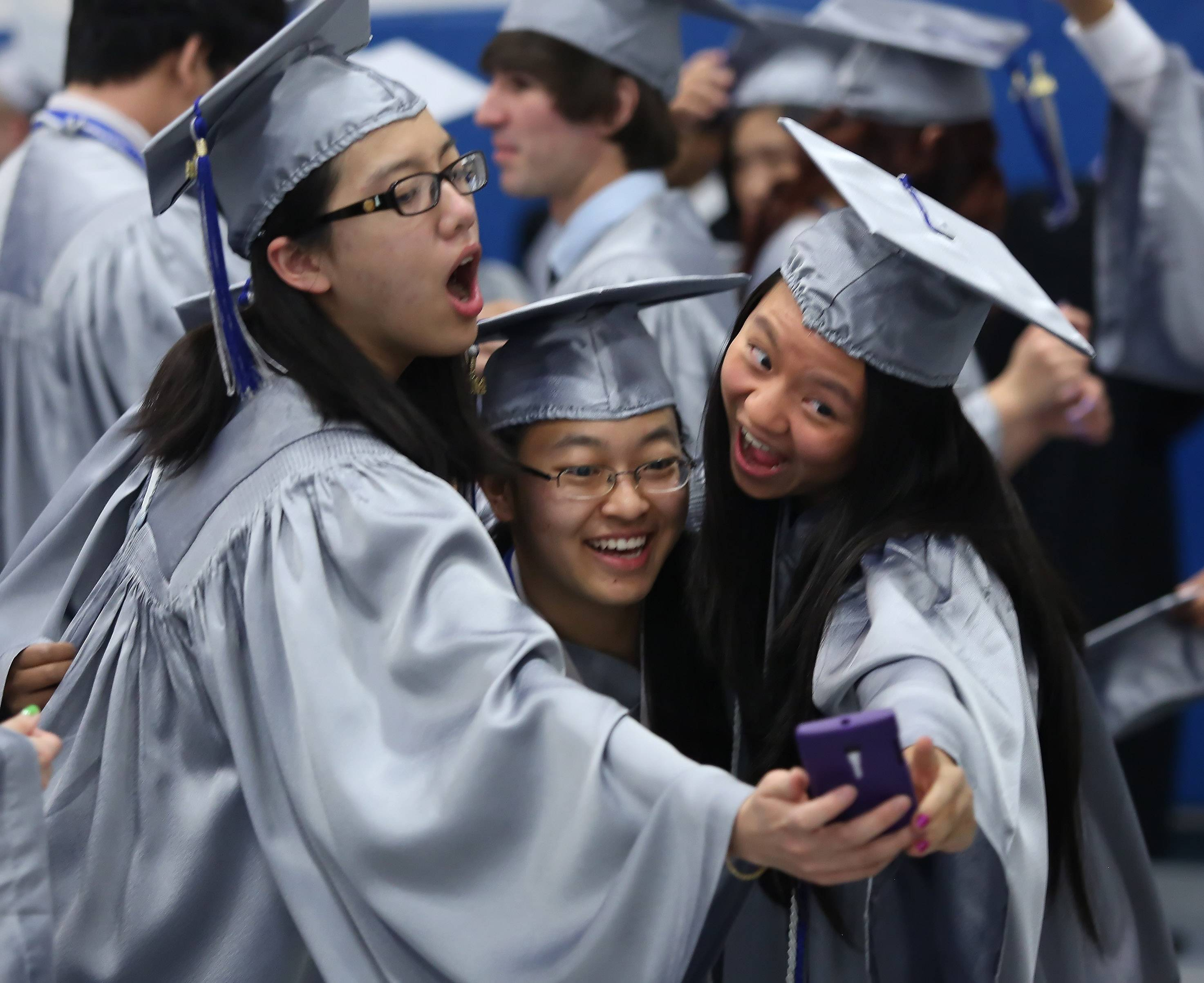 Ann Ho, left, and Suzie Chenand Alice Zhang take a picture with a cell phone.