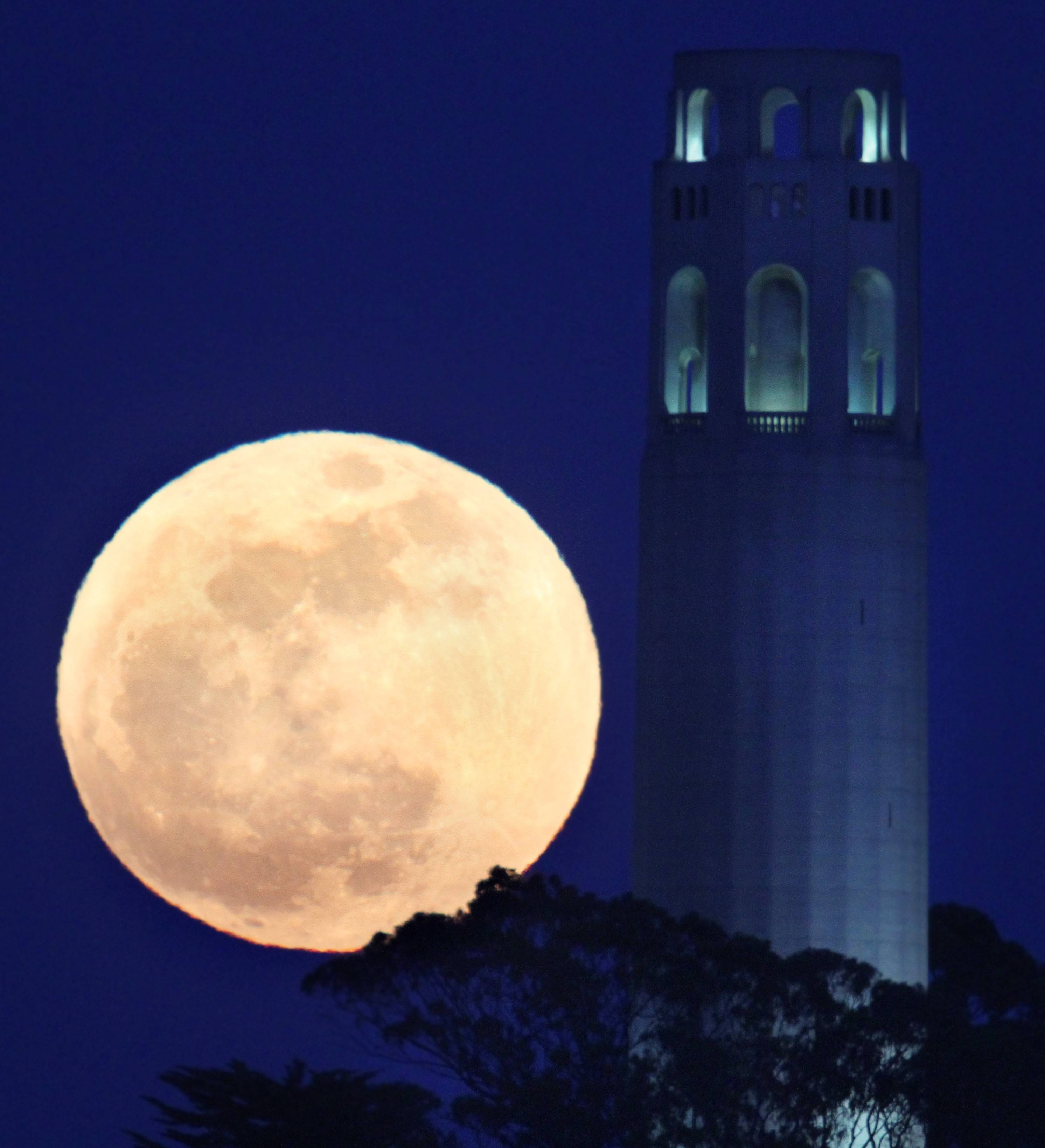 ASSOCIATED PRESS A full moon rises beside San Francisco's Coit Tower.