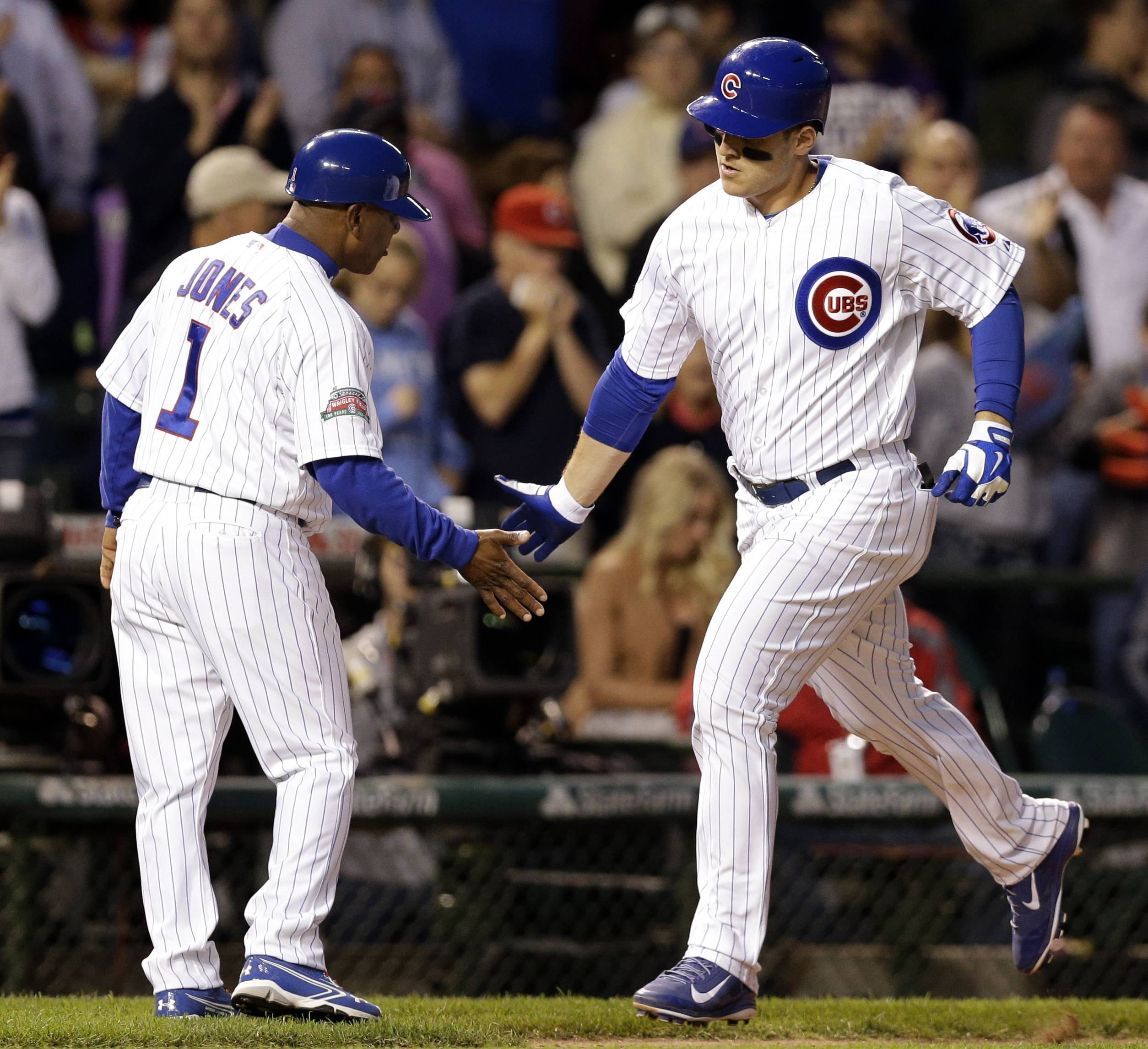 Chicago Cubs' Anthony Rizzo, right, celebrates with third base coach Gary Jones after hitting a solo home run during the seventh inning of a baseball game against the New York Mets in Chicago, Thursday, June 5, 2014. (AP Photo/Nam Y. Huh)