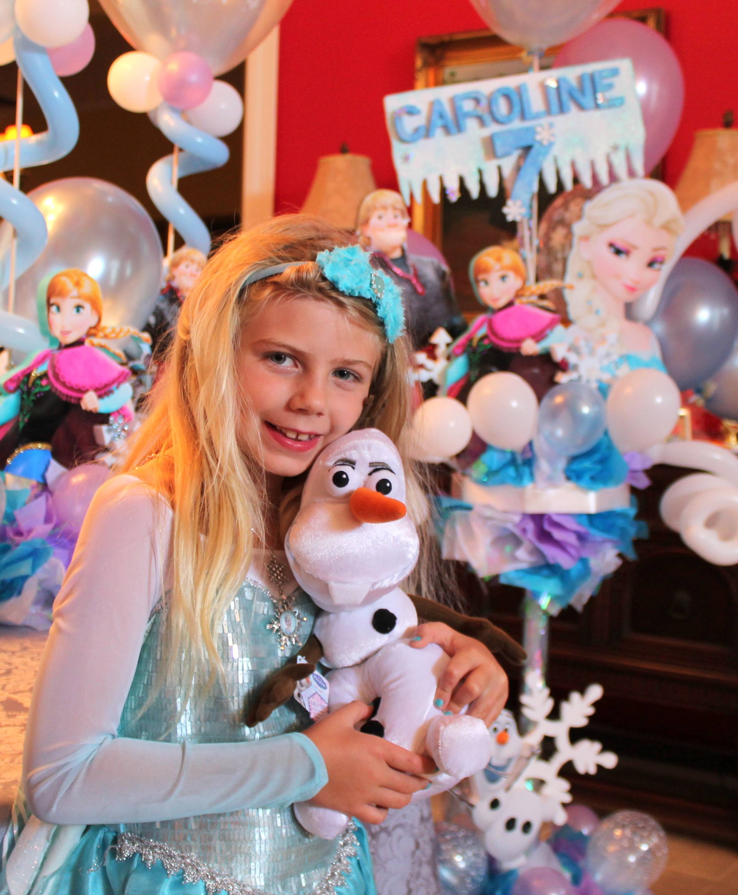 "Caroline Calder at her seventh birthday party themed after the Disney movie ""Frozen,"" in Boca Raton, Fla. Caroline is wearing a hard-to-find dress based on Princess Elsa's attire from the movie, and is holding a stuffed snowman named Olaf, who is a character in the film."