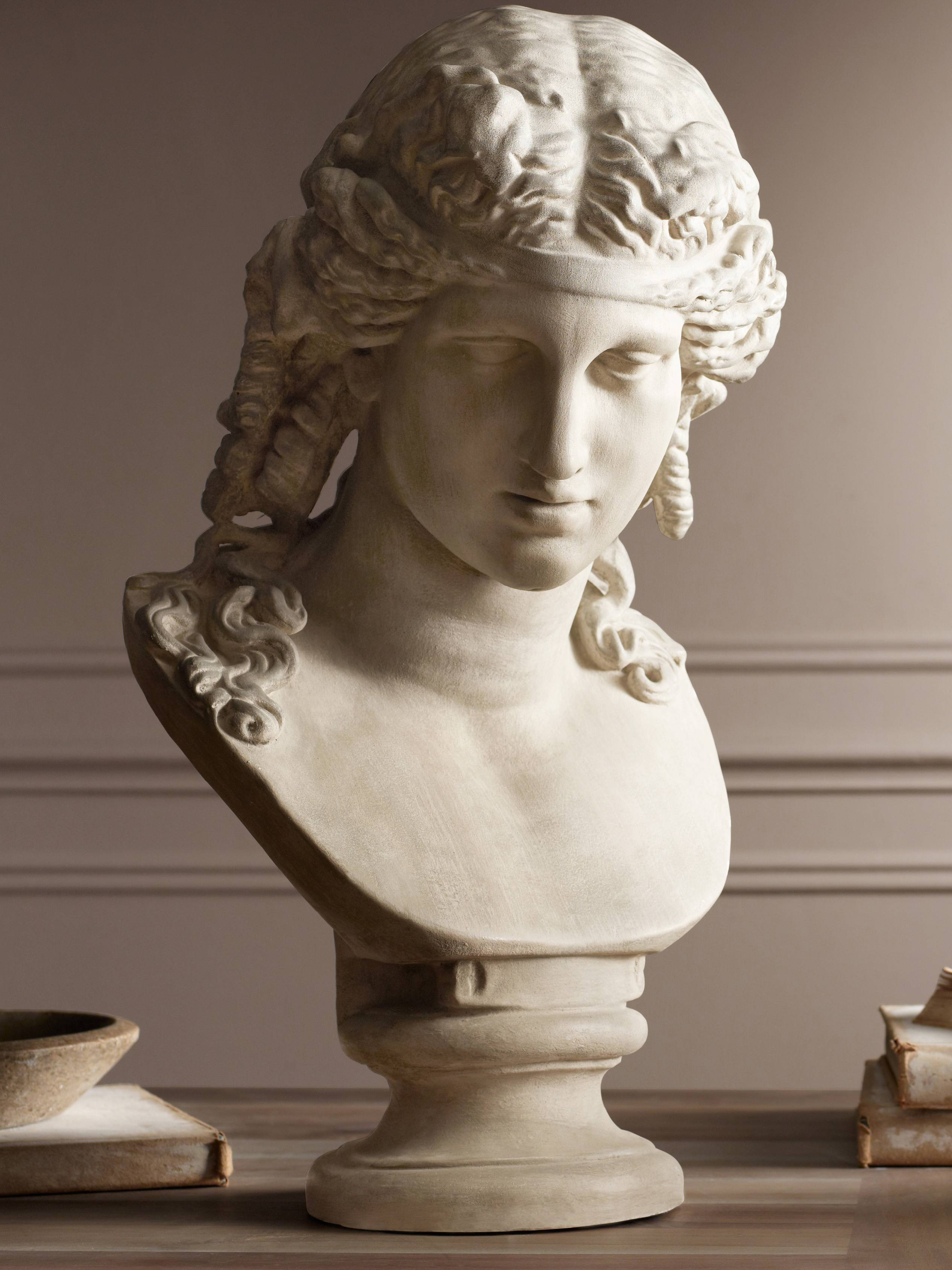 This bust of Ariadne is cast from plaster and hand rubbed to give it an aged look as an elegant objet d'art from the neoclassical era.