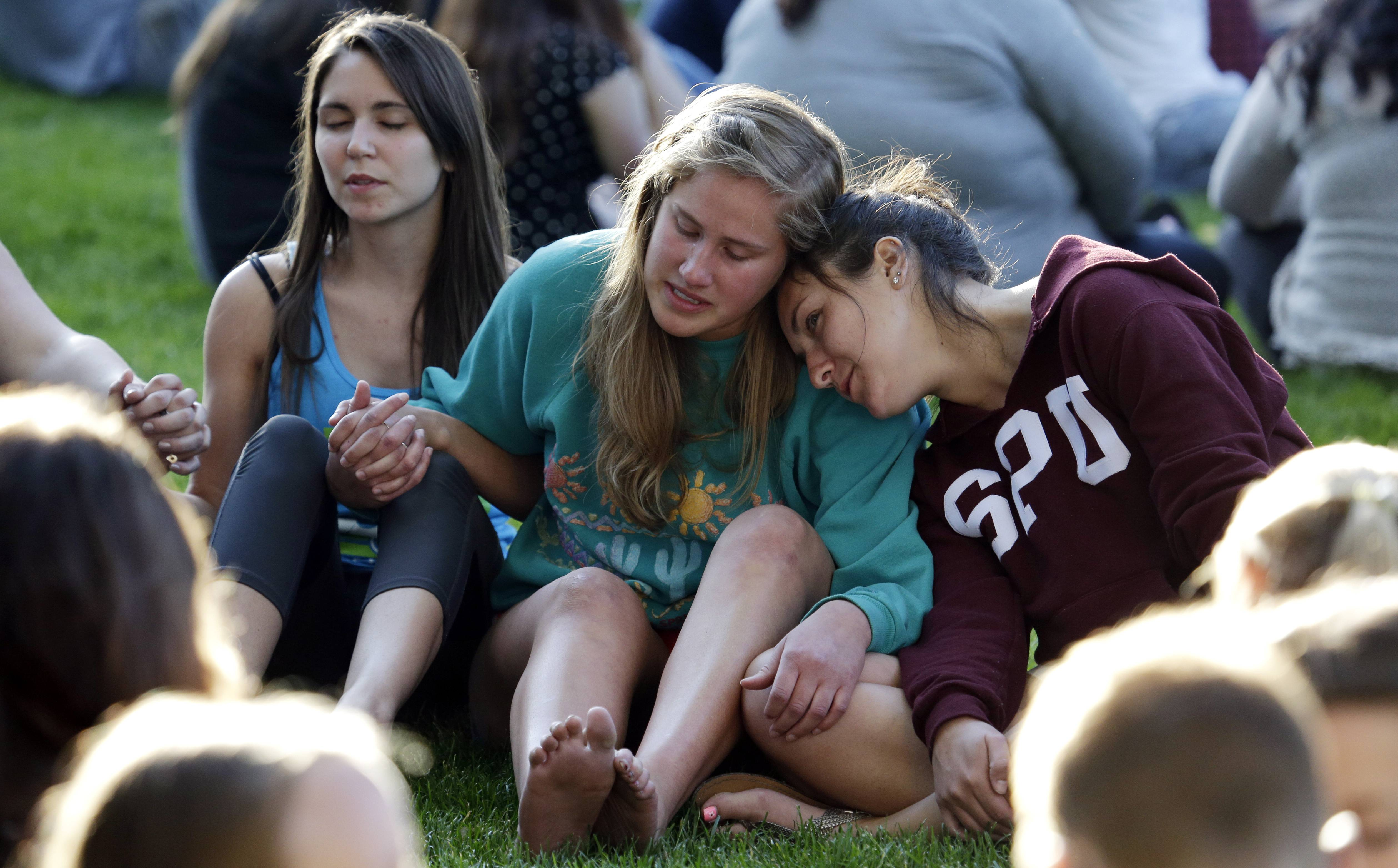 Students from Seattle Pacific University gather outside in a spontaneous prayer circle after a church service was full, after a shooting on the campus.