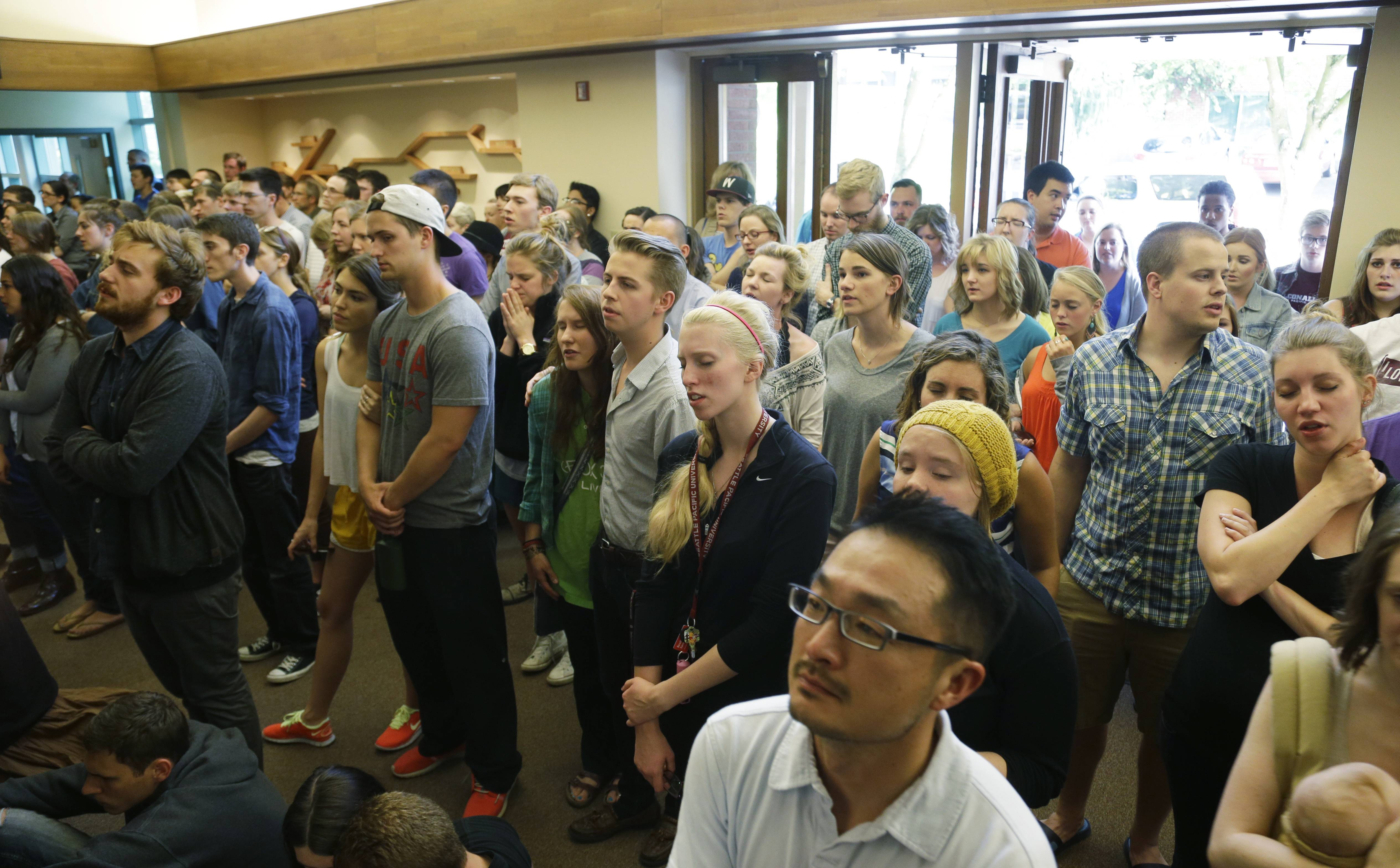 People stand in the foyer during a prayer service at the First Free Methodist Church Thursday at Seattle Pacific University in Seattle, where a shooting took place Thursday afternoon.