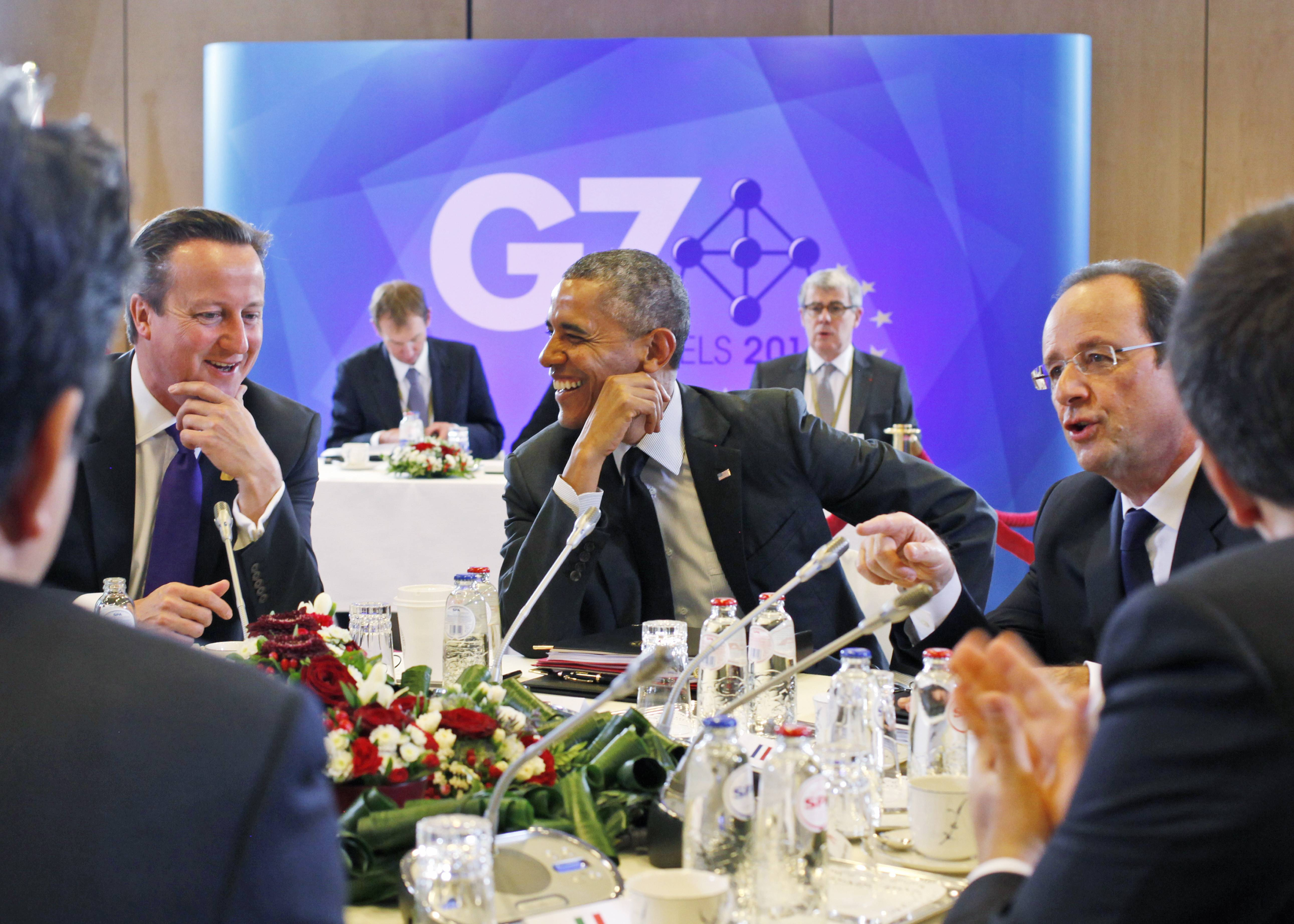 President Barack Obama jokes with British Prime Minister David Cameron, left, and French President Francois Hollande, right, during a G7 session in Brussels, Belgium, Thursday.