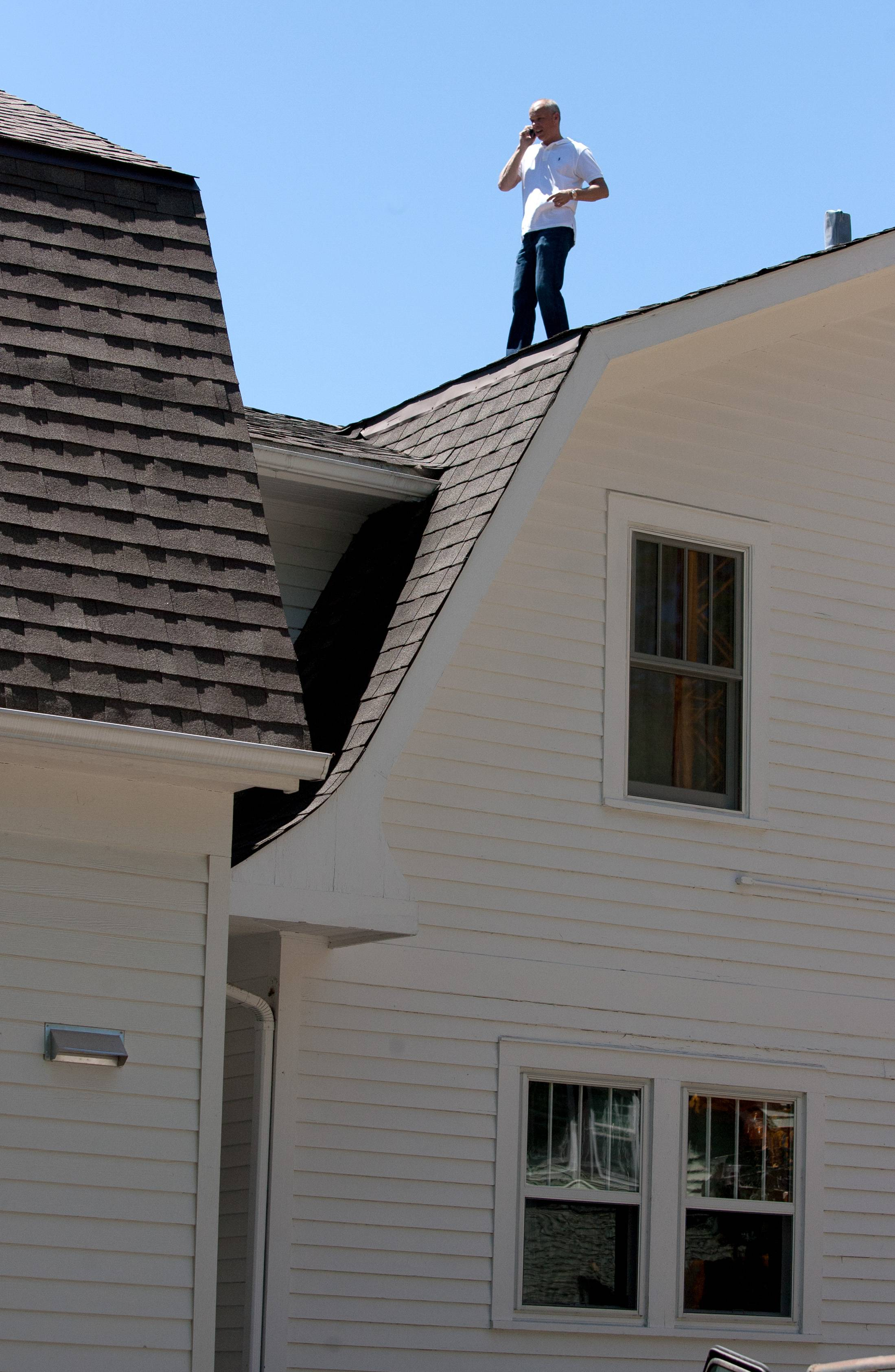Greg Morey surveys the roofline after moving a coach house from next door to his family's Glen Ellyn property.