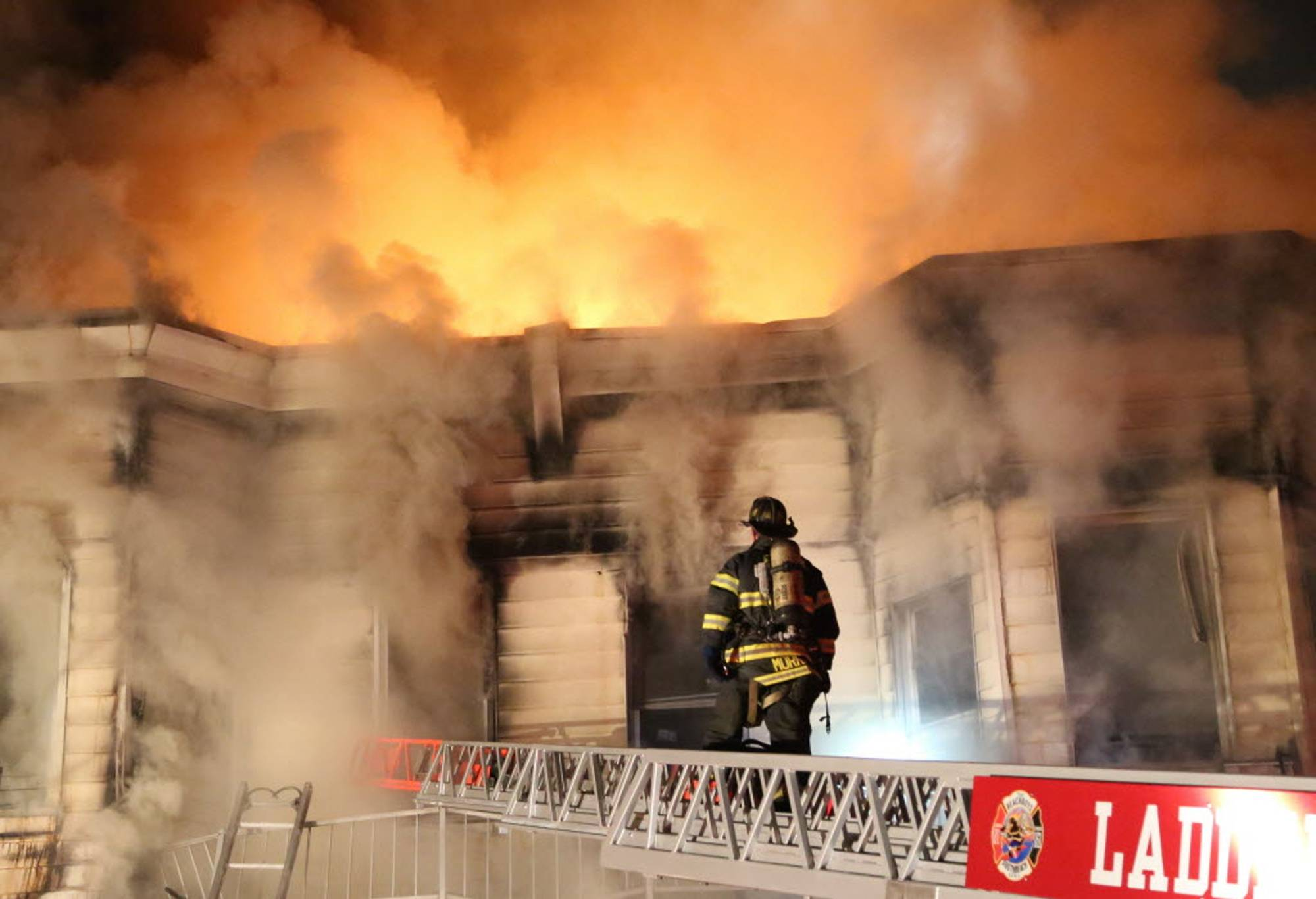 At least 34 people were injured in a fire that tore through three townhouses on New York City's Staten Island early Thursday, including two young children who were tossed out of a smoke-filled second-floor window into the arms of neighbors below, authorities and witnesses said.