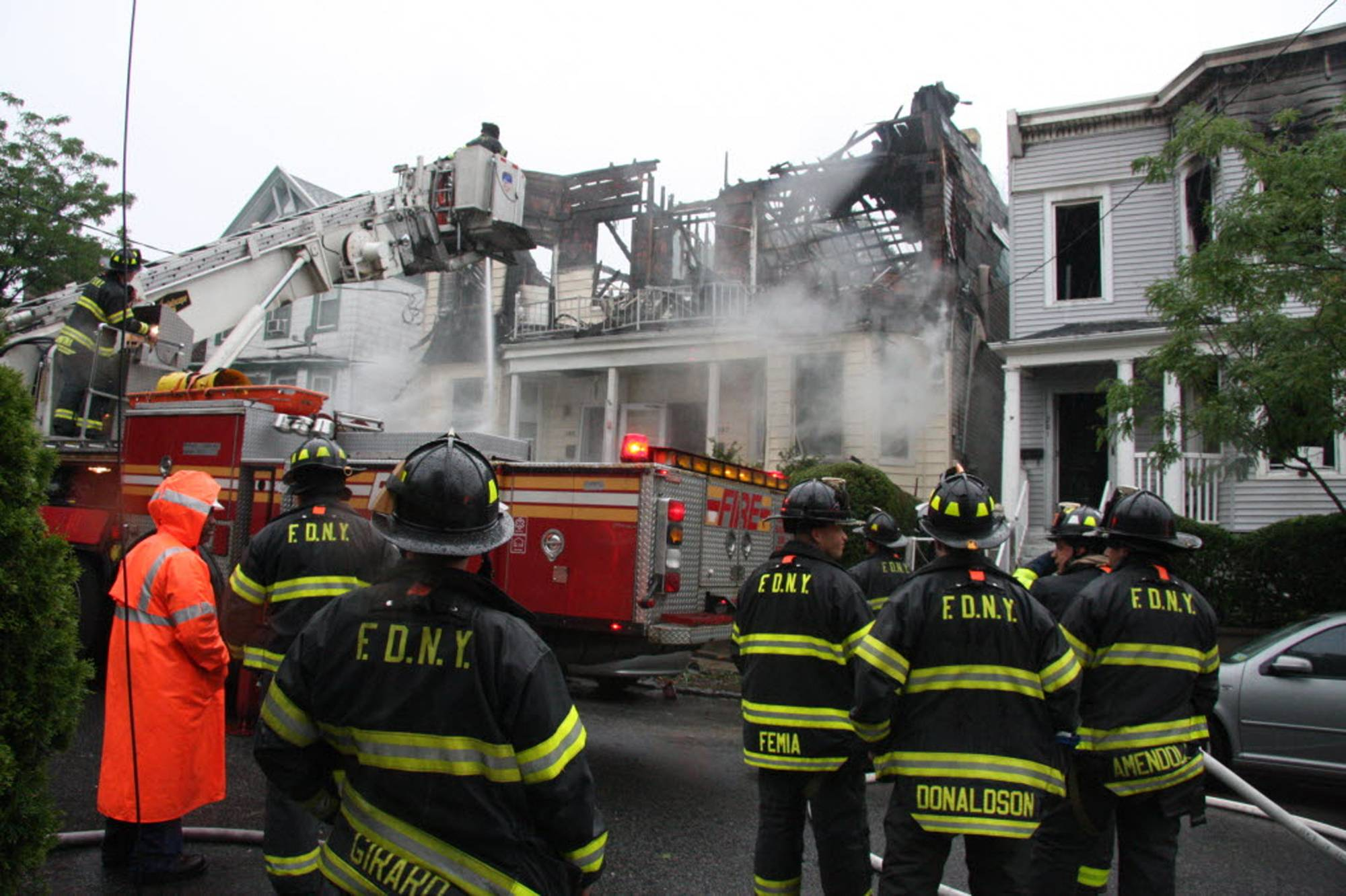Firefighters continue working the scene of a fire that tore through three townhouses on New York City's Staten Island early Thursday, June 5, 2014.