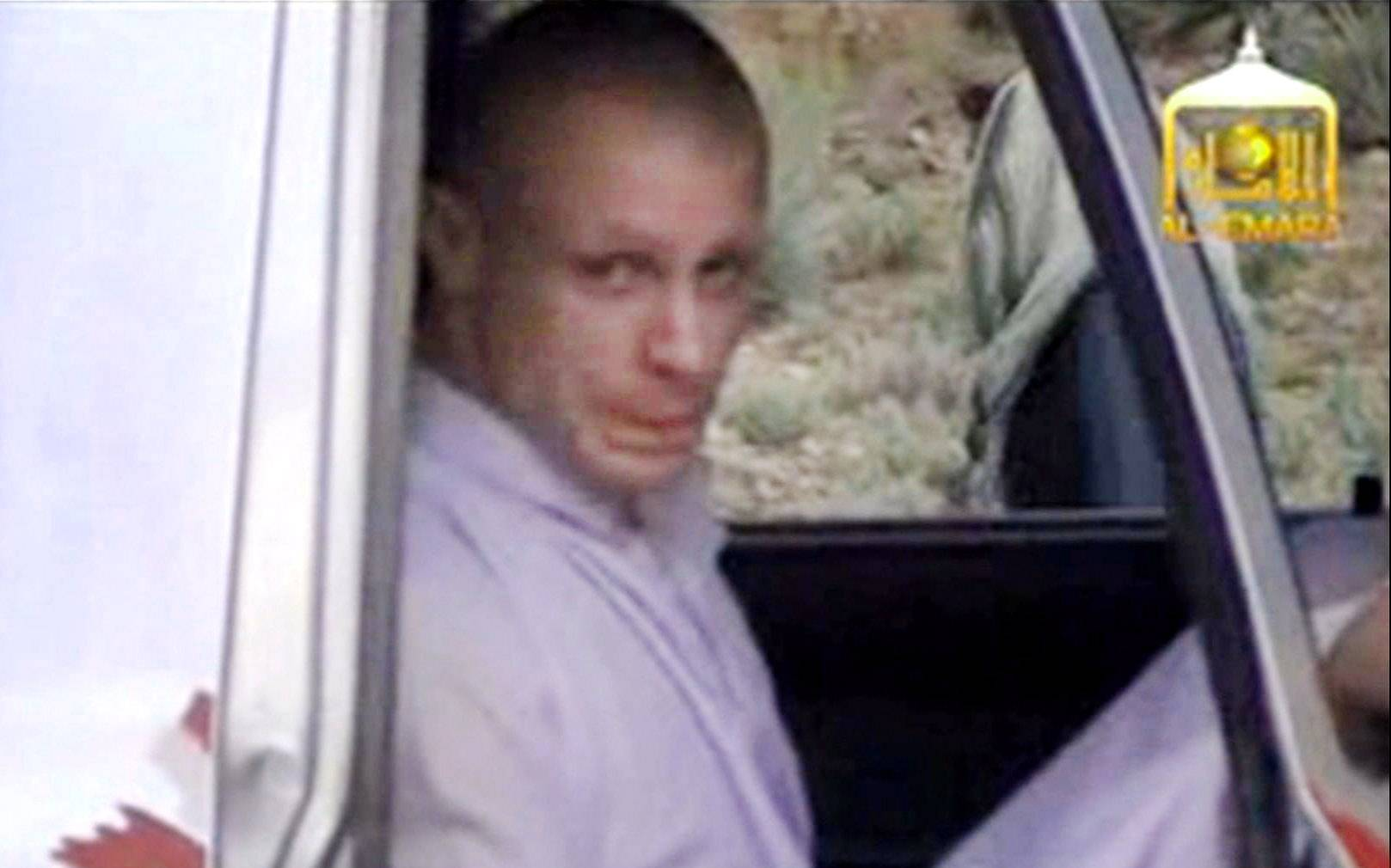 In this image taken from video, Sgt. Bowe Bergdahl sits in a vehicle guarded by the Taliban in eastern Afghanistan during his release. More than a dozen Taliban fighters with machine guns were seen around the truck and nearby.