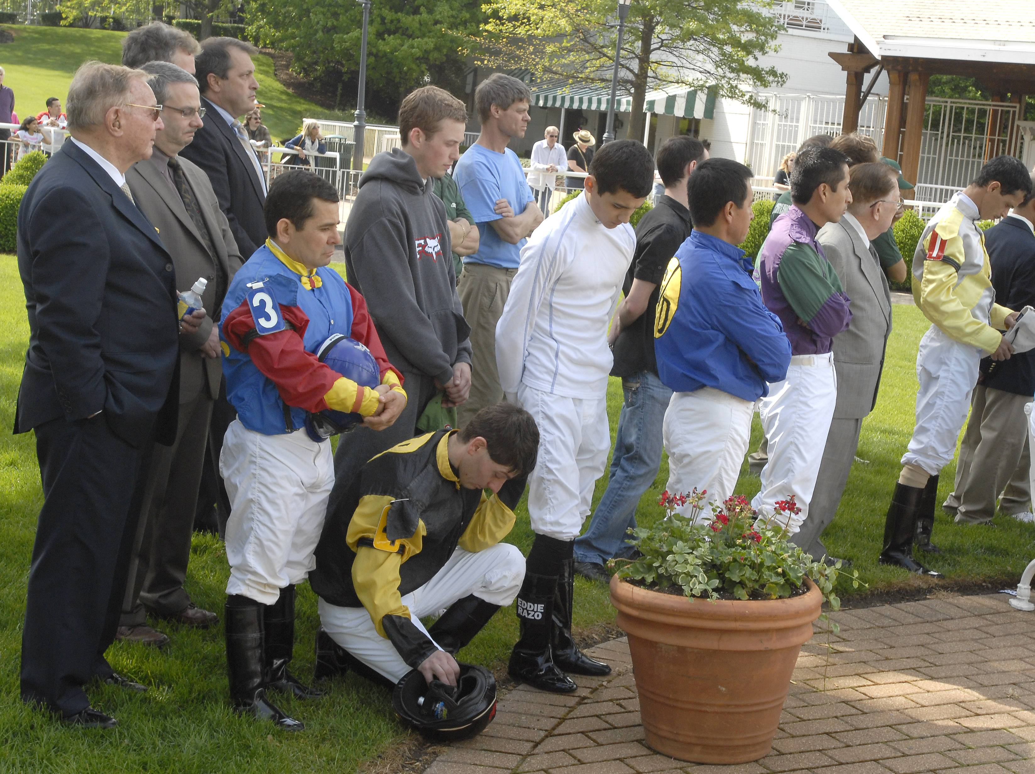 "Richard Duchossois, chairman of Arlington International Racecourse, far left, stands with jockeys and other track personnel for a moment of silence for Eusebio ""Eddie"" Razo Jr. in 2012."