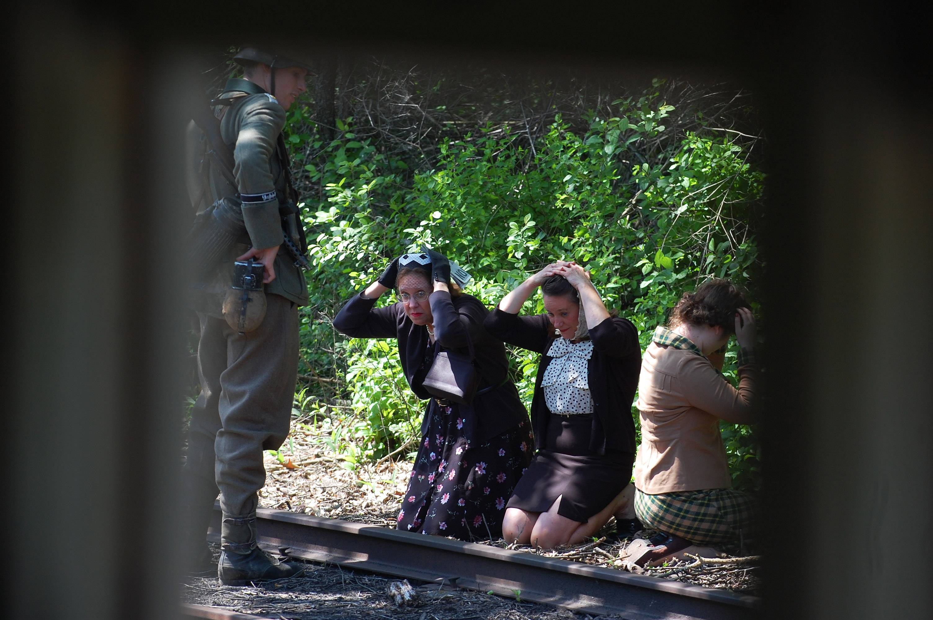 French civilians are pulled off the train by a German soldier and questioned in a scene from last year's 'Rails to Victory' at the Fox River Trolley Museum in South Elgin. This re-enactment takes its audience on a trolley tour of Occupied France, recreating the European interurban rail line that ran between Paris and Rouen, along the Seine River, during the summer of 1944.