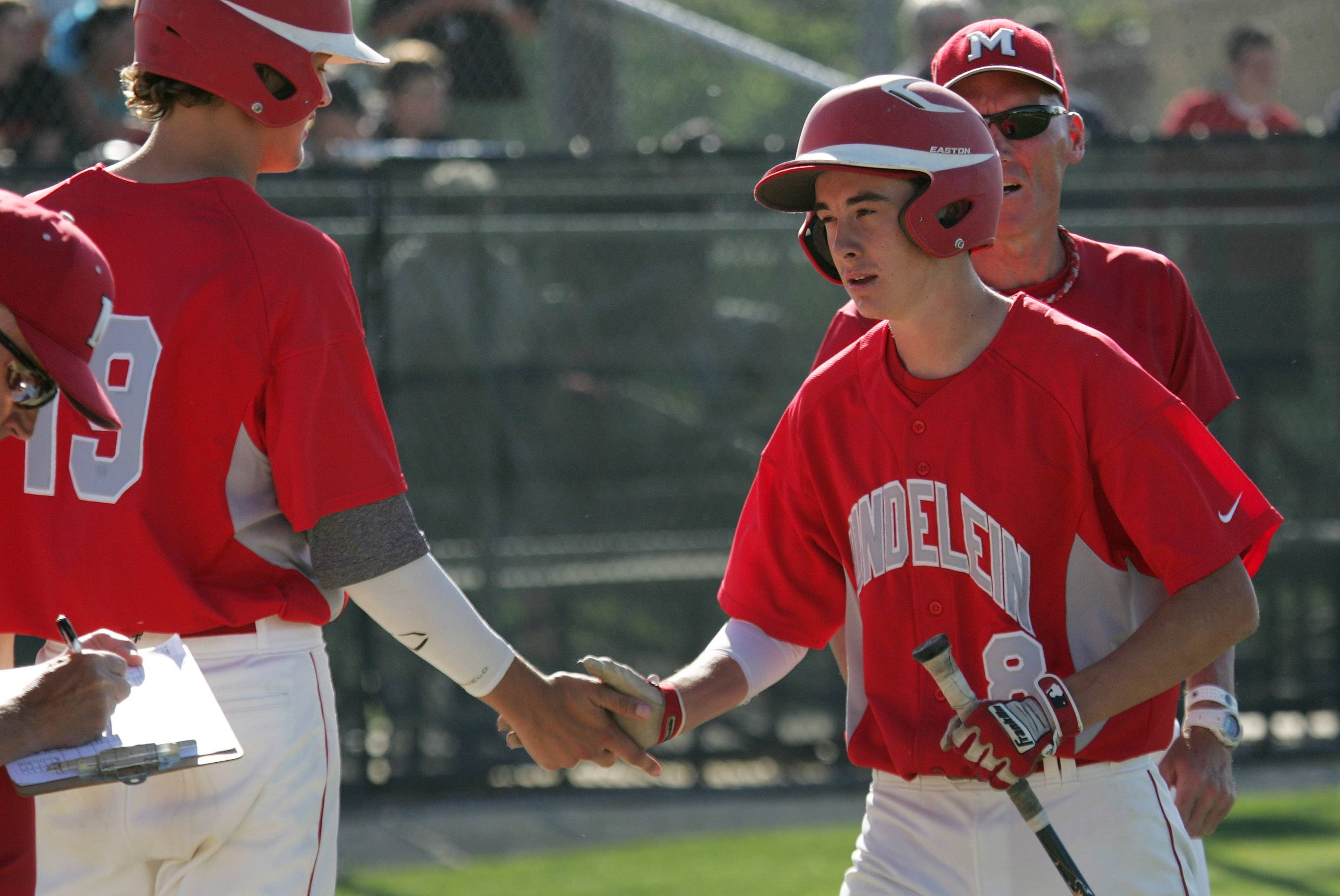 Mundelein's Derek Parola, right, is congratulated by teammate Reese Dolan after scoring a run in the third inning against Glenbrook South in Class 4A baseball sectional semifinal action Thursday in in Glenview.