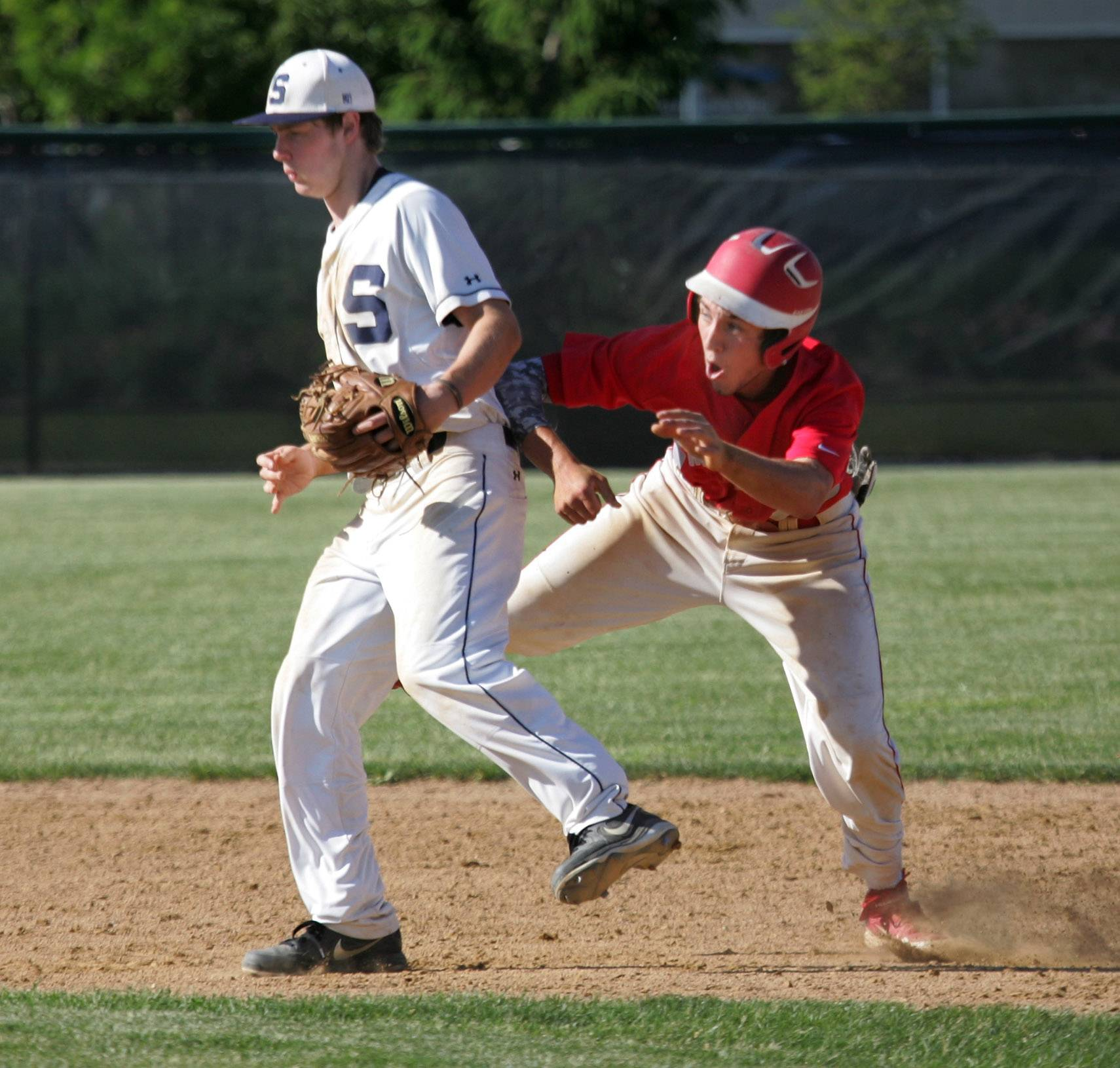 Mundelein runner Mike Metz is interfered with by Glenbrook South second baseman Jimmy Ruddy as he runs to third base during the Class 4A baseball sectional semifinal Thursday in Glenview.
