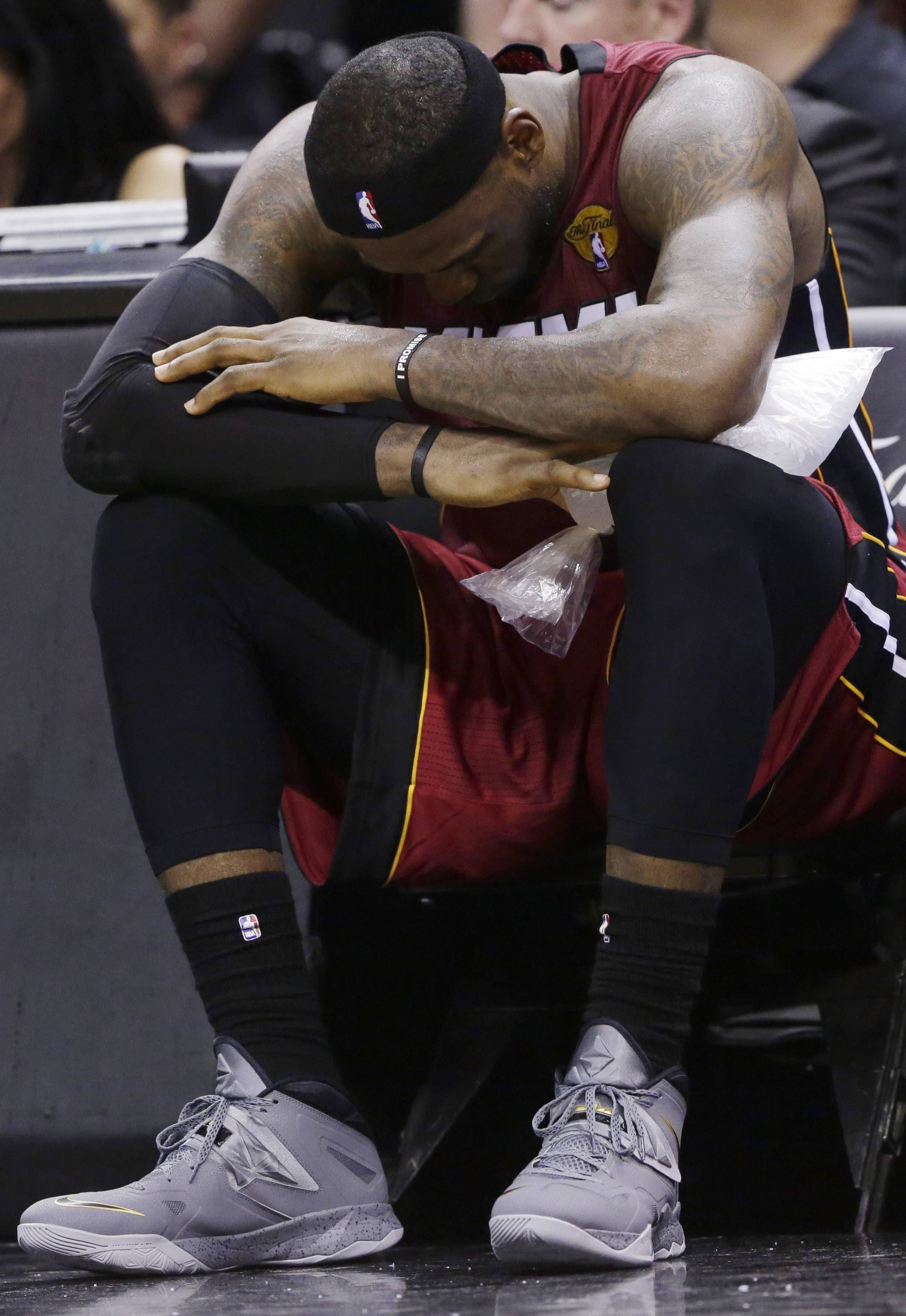 LeBron James sits with ice on his leg after injuring himself against the San Antonio Spurs during the second half in Game 1 of the NBA basketball finals on Thursday.