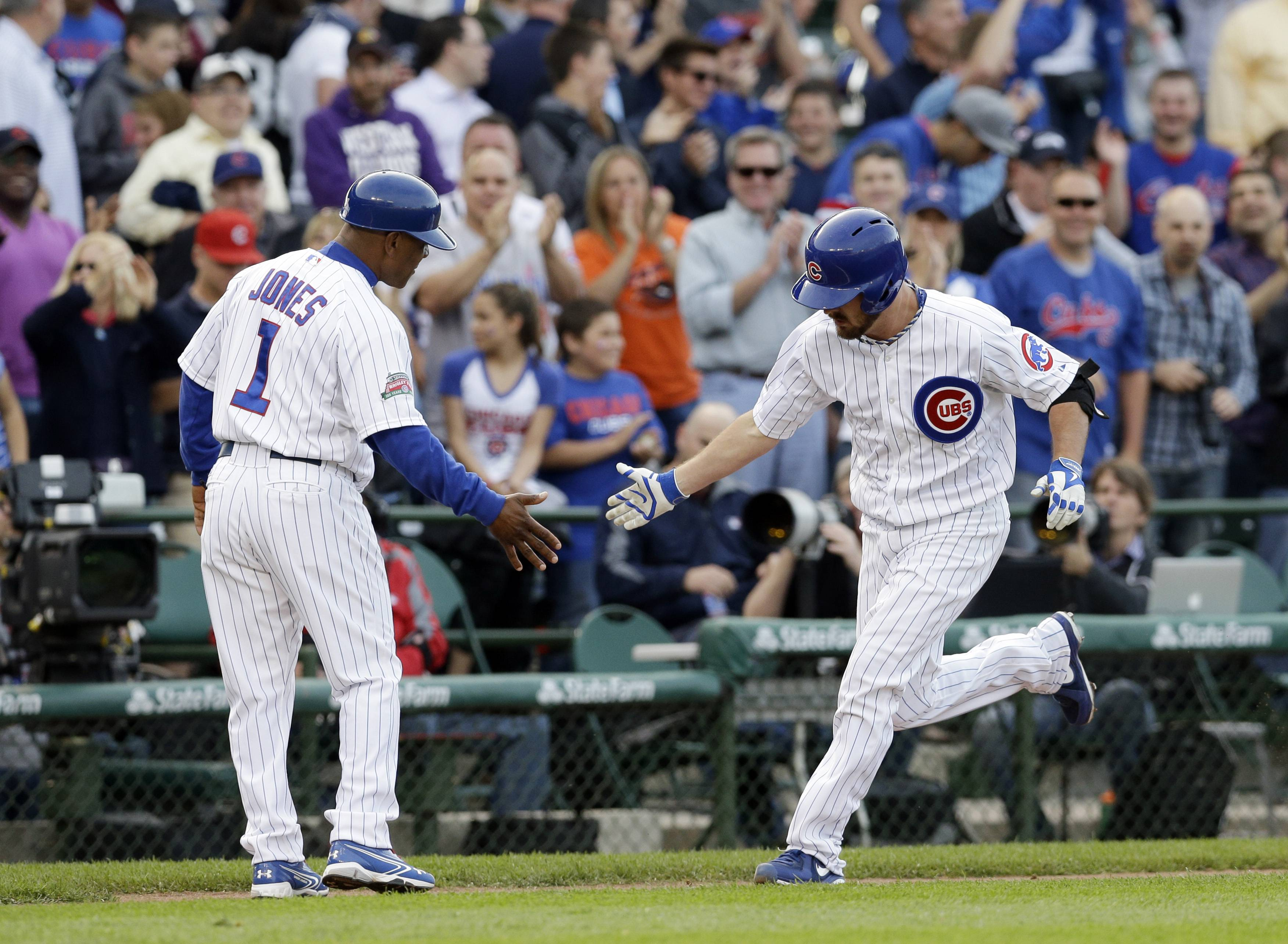 Cubs starter Travis Wood, right, celebrates with third base coach Gary Jones after hitting a 2-run homer in the second inning Thursday against the Mets at Wrigley Field.