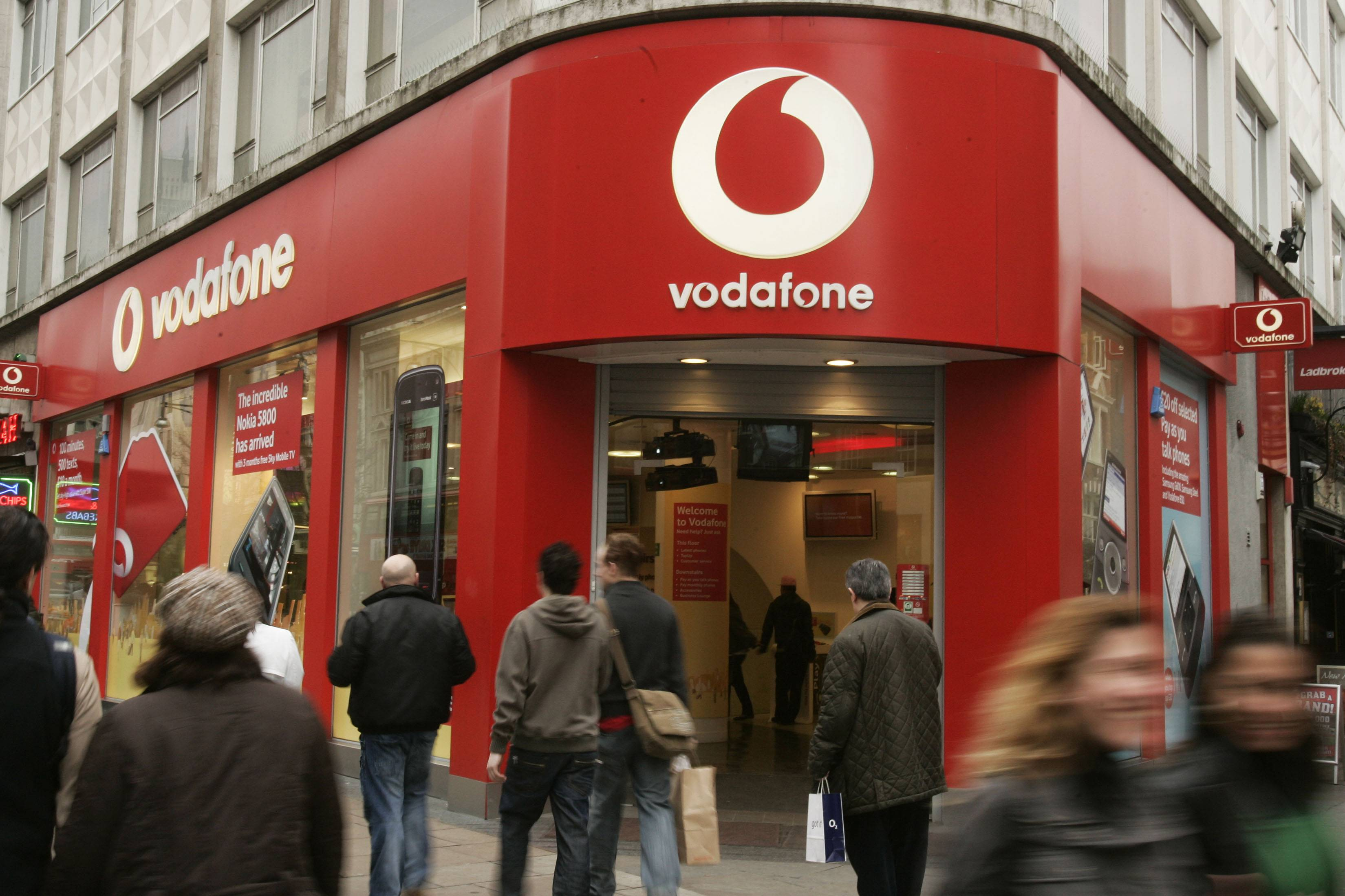 People walk by a branch of Vodafone in central London. Vodafone, one of the world's largest cellphone companies, revealed the scope of government snooping into phone networks Friday.