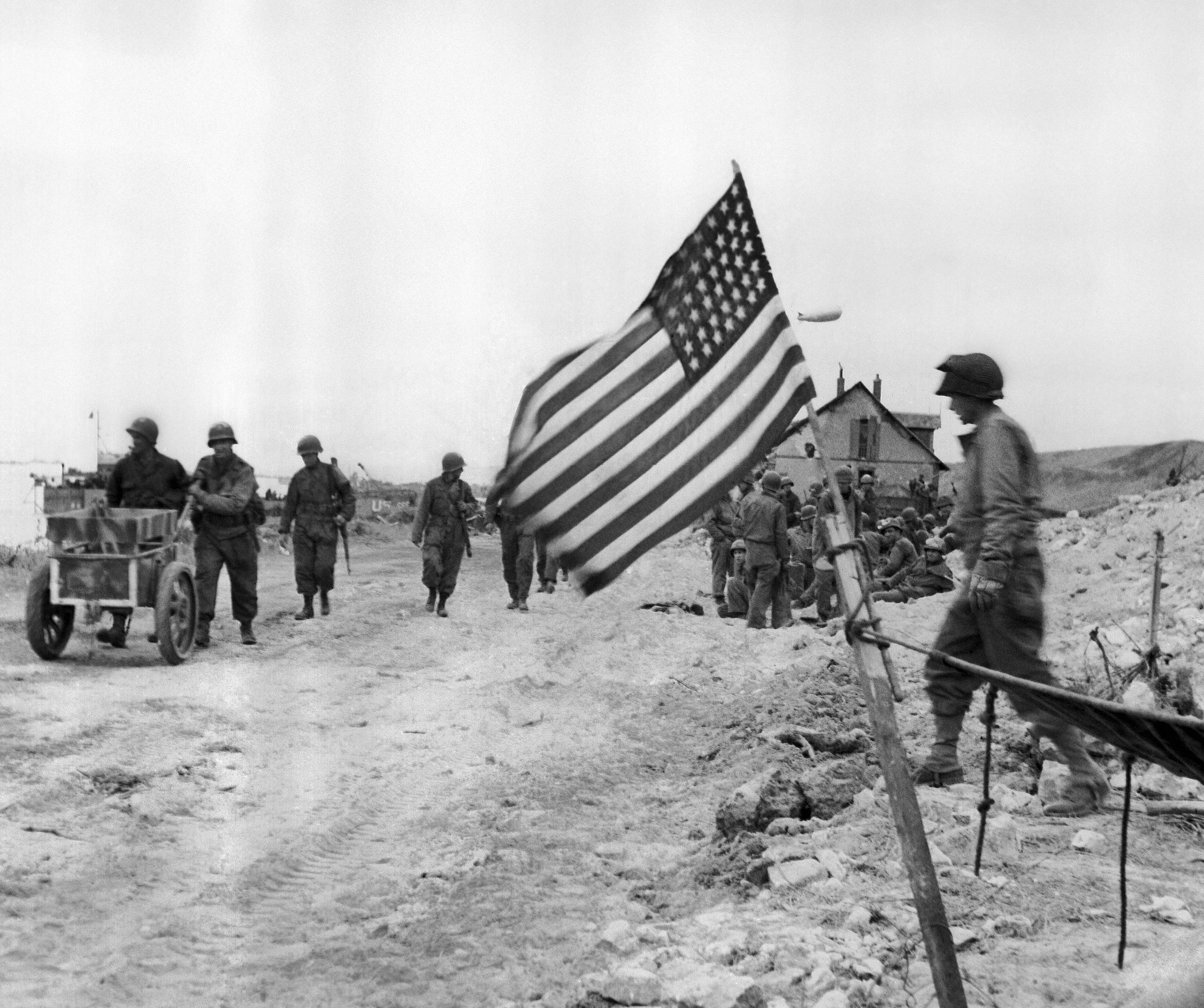 The American flag flies from a make-shift staff on a beach on the French Normandy coast on June 14, 1944 where allied troops fought bitterly to push back the Germans. Americans in background push a captured German ammunition cart.