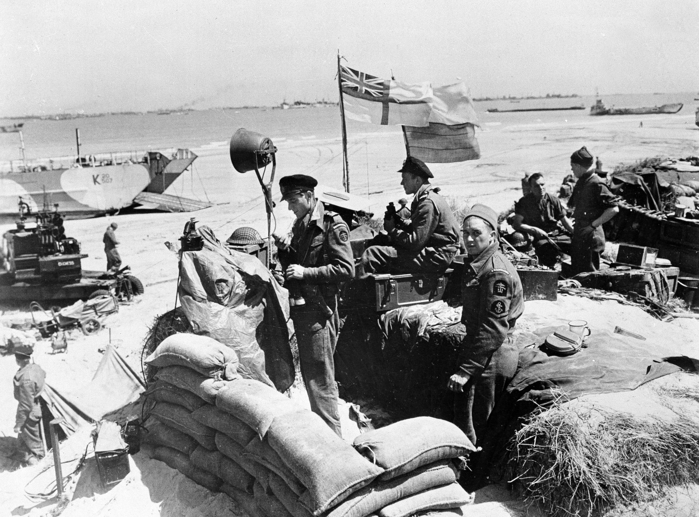 British troops make their way through low water and up the beach after leaving landing craft which transported them across the Channel to the Normandy beachhead for D-Day invasion in France, June 6, 1944 in World War II.