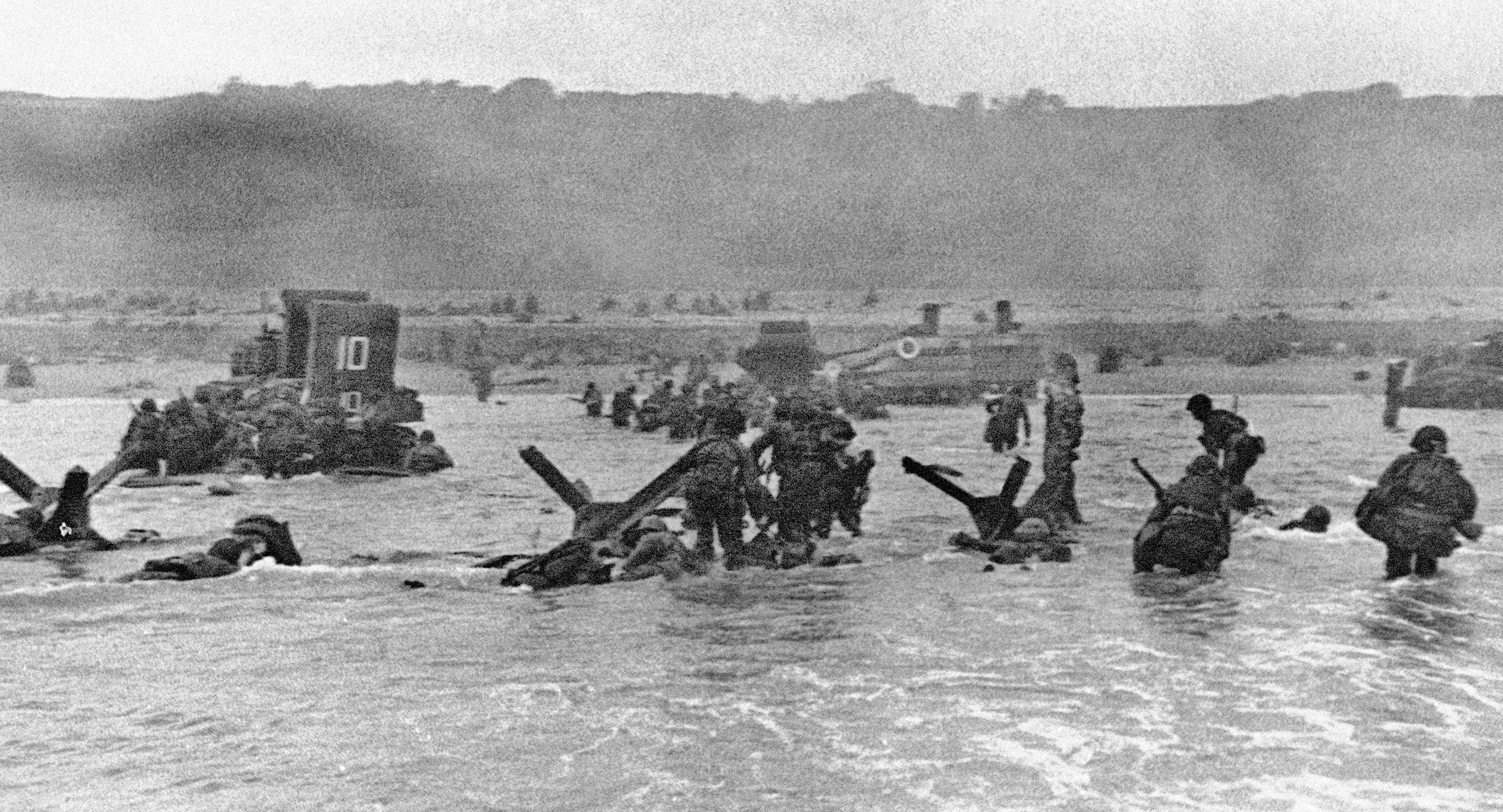 In this June 6, 1944, photo, some of the first troops to hit the Normandy, France, beachhead take cover behind enemy obstacles to fire on German forces as others follow the first tanks plunging through the water.